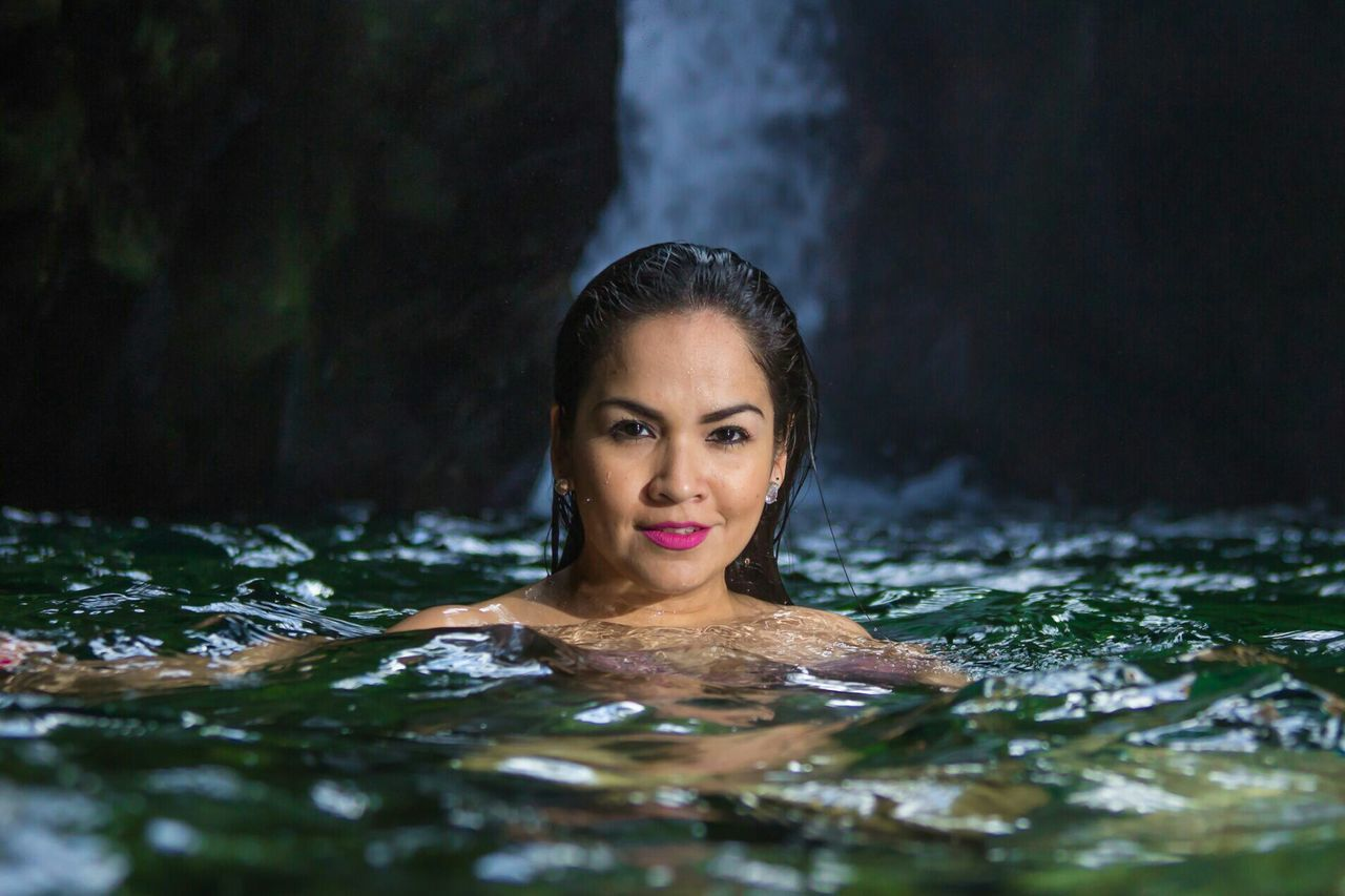 Portrait Of Beautiful Woman Swimming In Lake At Forest