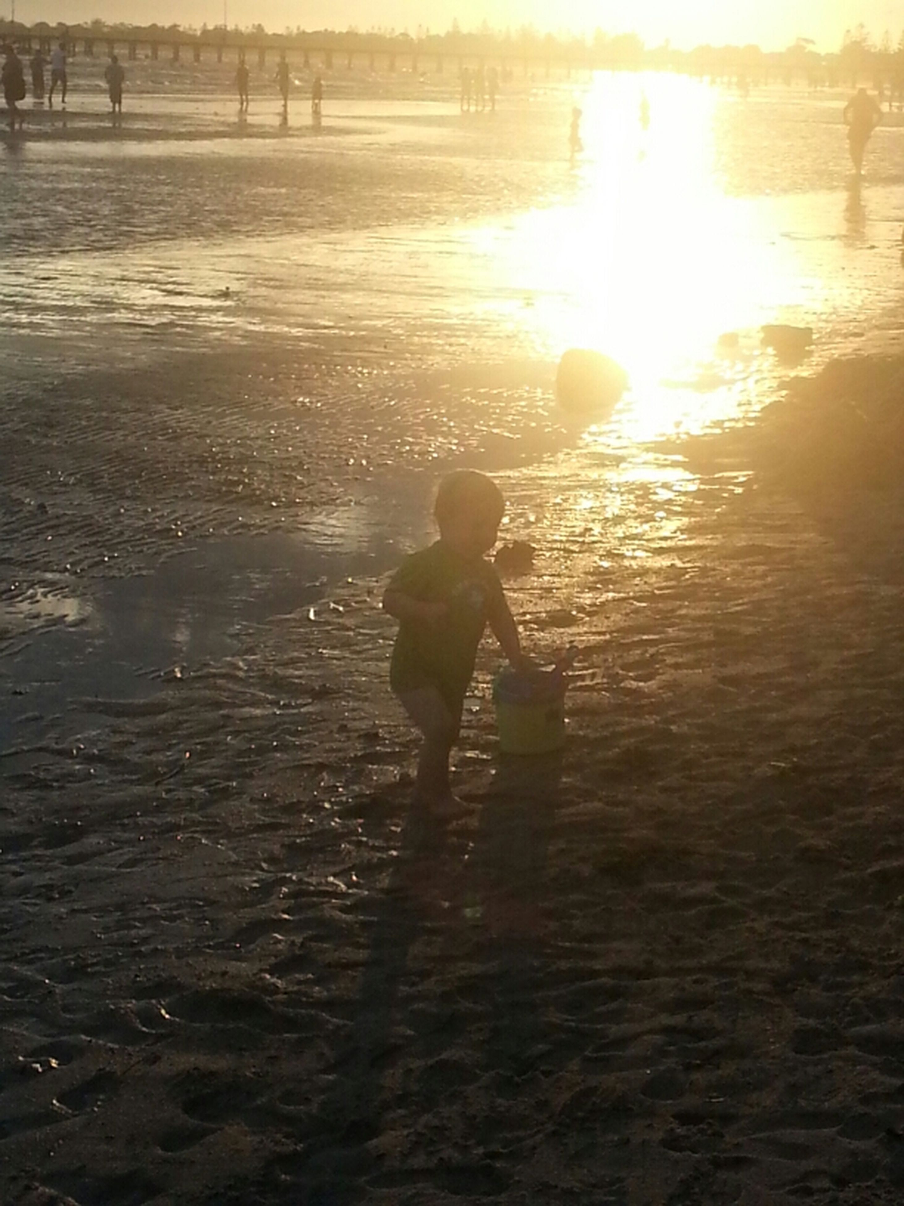 water, lifestyles, leisure activity, sunlight, sun, childhood, reflection, sunset, full length, beach, tranquility, nature, boys, girls, tranquil scene, beauty in nature, sea, standing