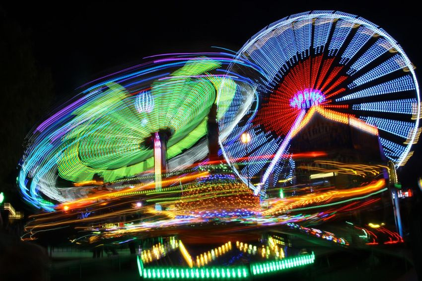 Amusement Park Ferris Wheel Night Arts Culture And Entertainment Illuminated Amusement Park Ride Multi Colored Long Exposure Light Trail Motion No People Clear Sky Sky Outdoors City Carousel City Focus On Foreground Close-up Connected By Travel
