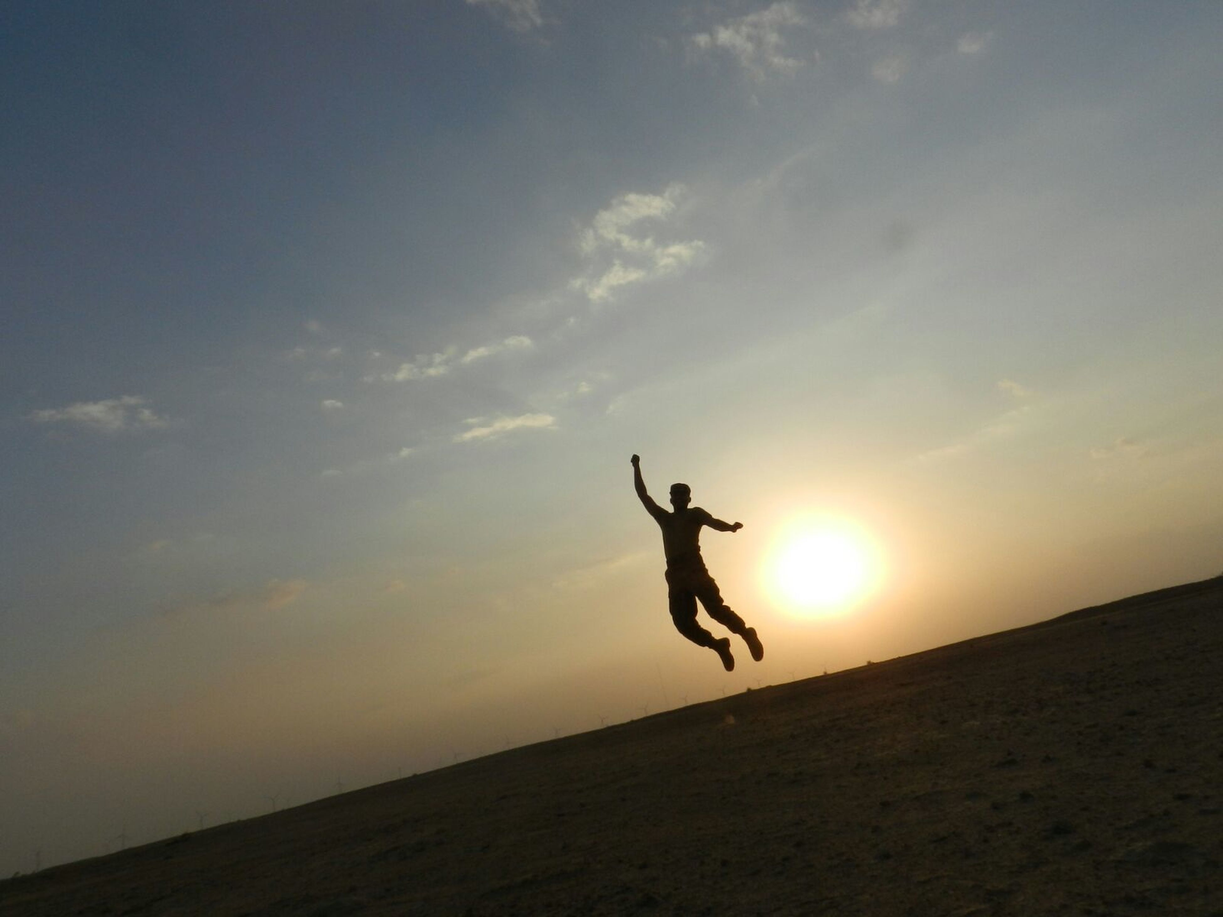 mid-air, silhouette, full length, sunset, jumping, sky, leisure activity, lifestyles, flying, sun, freedom, extreme sports, nature, arms outstretched, motion, landscape, sunlight, scenics