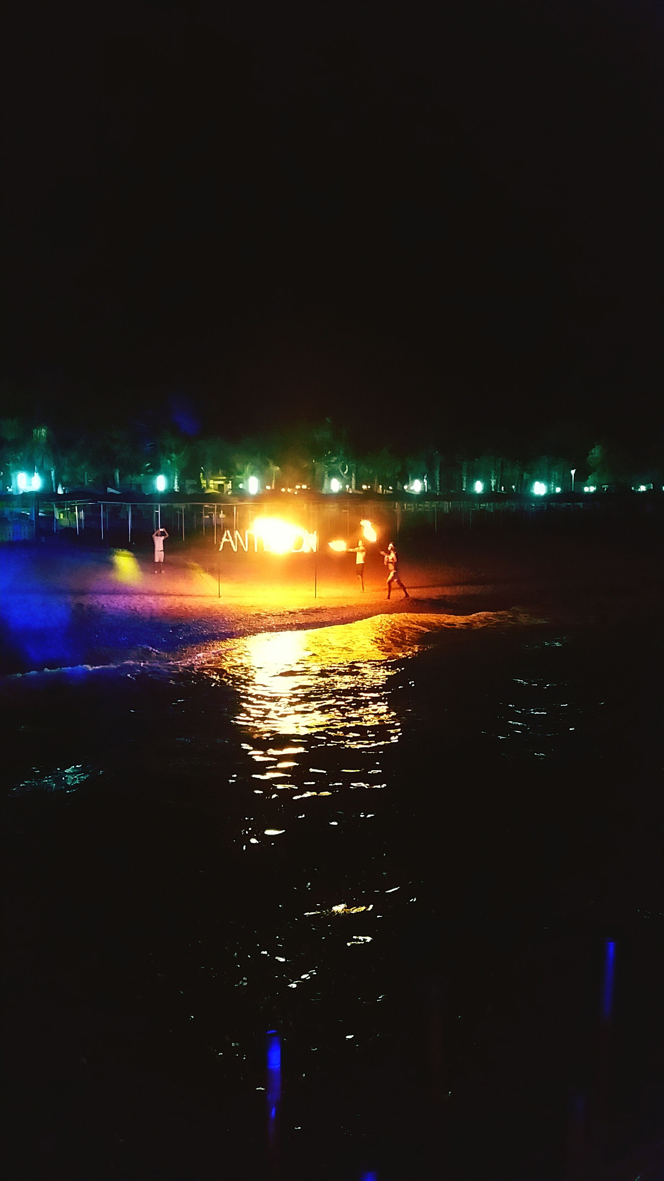 illuminated, night, reflection, water, dark, city, sea, waterfront, tranquil scene, scenics, sky, outdoors, calm, tranquility, multi colored, atmospheric mood, city life, vacations, outline, colorful, ocean, no people