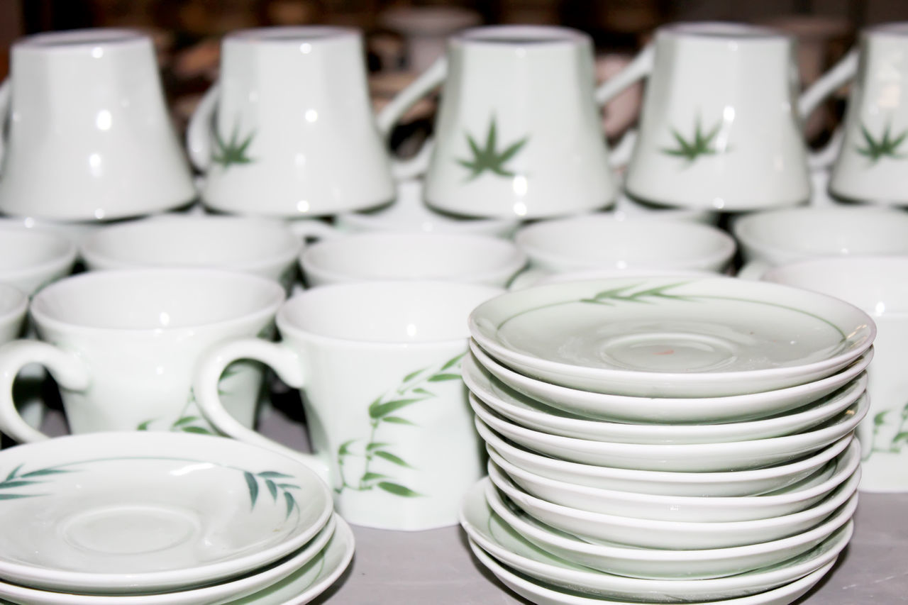 indoors, white color, large group of objects, bowl, close-up, focus on foreground, no people, arrangement, plate, stack, day