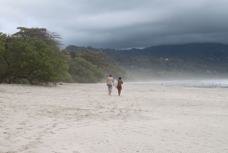 Manzanillo Beach Surf Adult Beach Beauty In Nature Before The Storm Day Friendship Full Length Leisure Activity Lifestyles Mountain Nature Outdoors People Playing Real People Sand Scenics Sea Sky Surfing In Costa Rica Togetherness Tranquility Tree Tropical Shower Tropical Storm