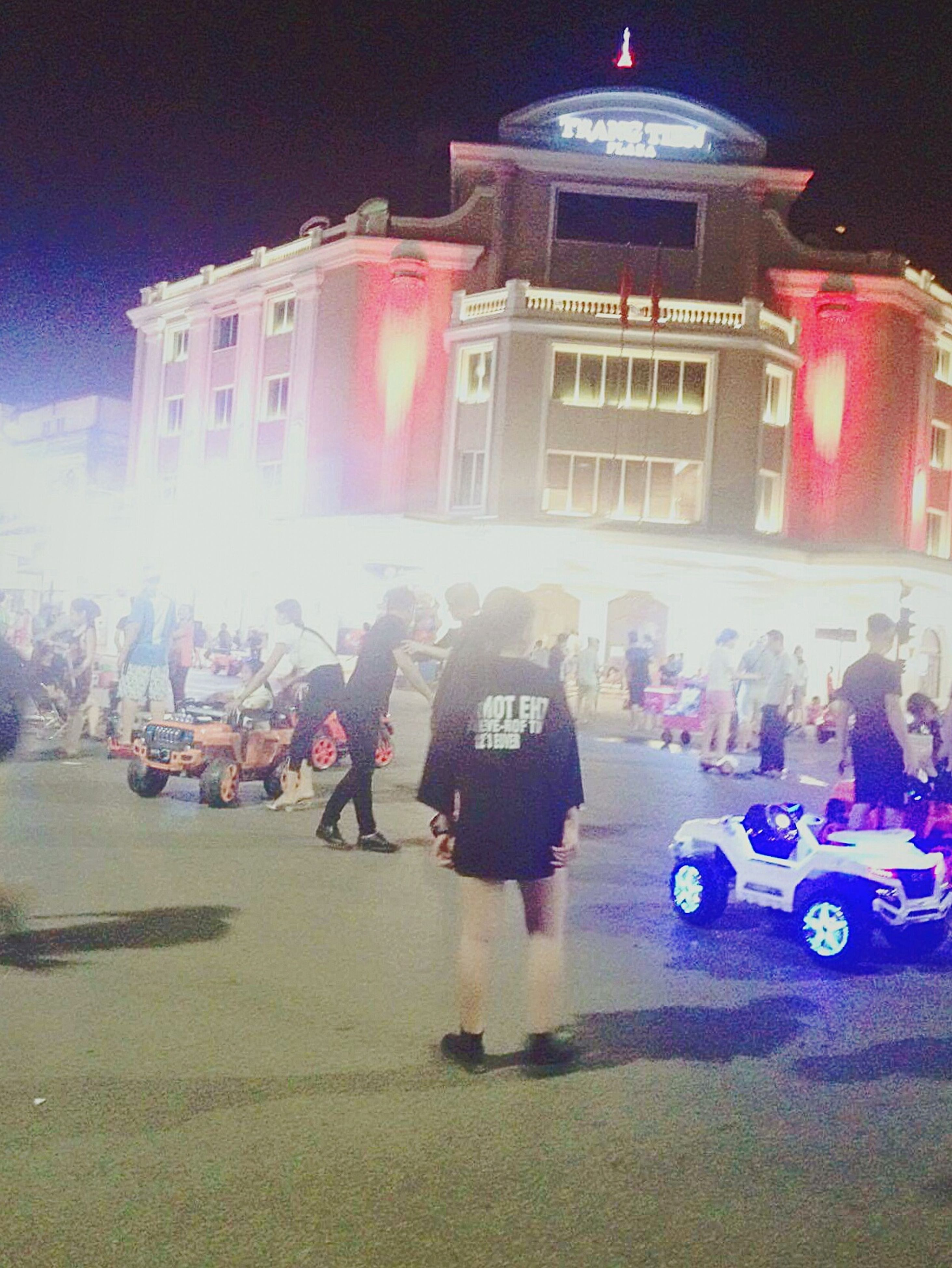 building exterior, built structure, architecture, real people, large group of people, illuminated, night, land vehicle, street, car, lifestyles, city, outdoors, women, men, crowd, sky, people