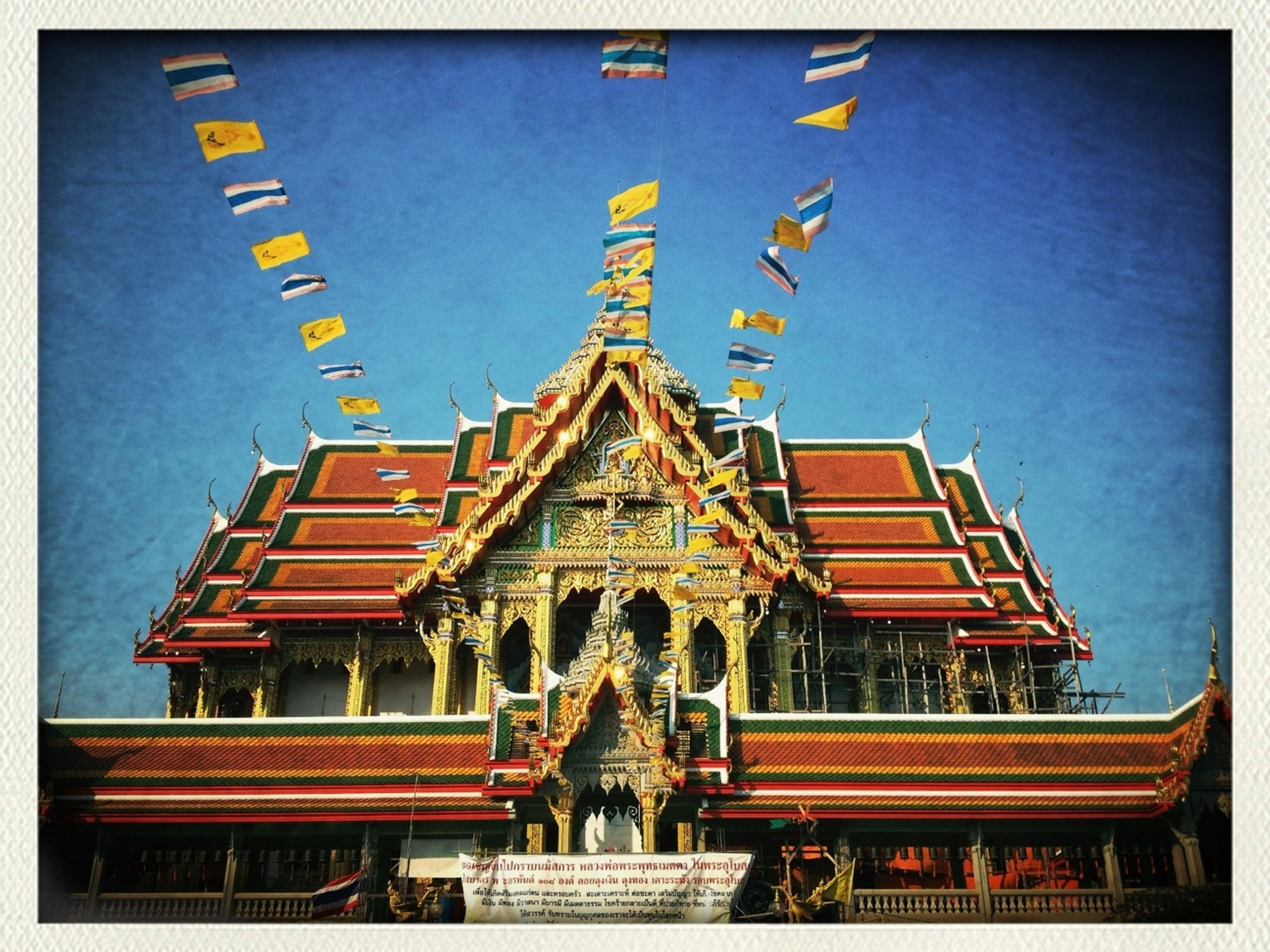 architecture, built structure, religion, building exterior, spirituality, place of worship, art and craft, transfer print, human representation, temple - building, low angle view, art, famous place, travel destinations, statue, sculpture, clear sky, creativity, temple