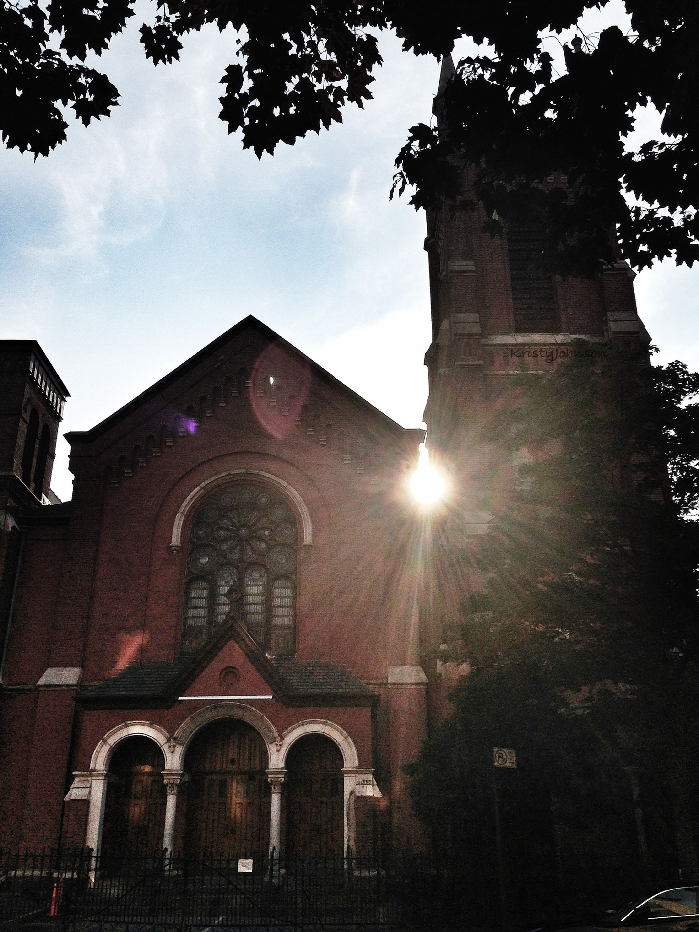 architecture, religion, place of worship, building exterior, built structure, spirituality, church, low angle view, cathedral, sky, history, tree, sunlight, sun, old, cross, sunbeam, outdoors