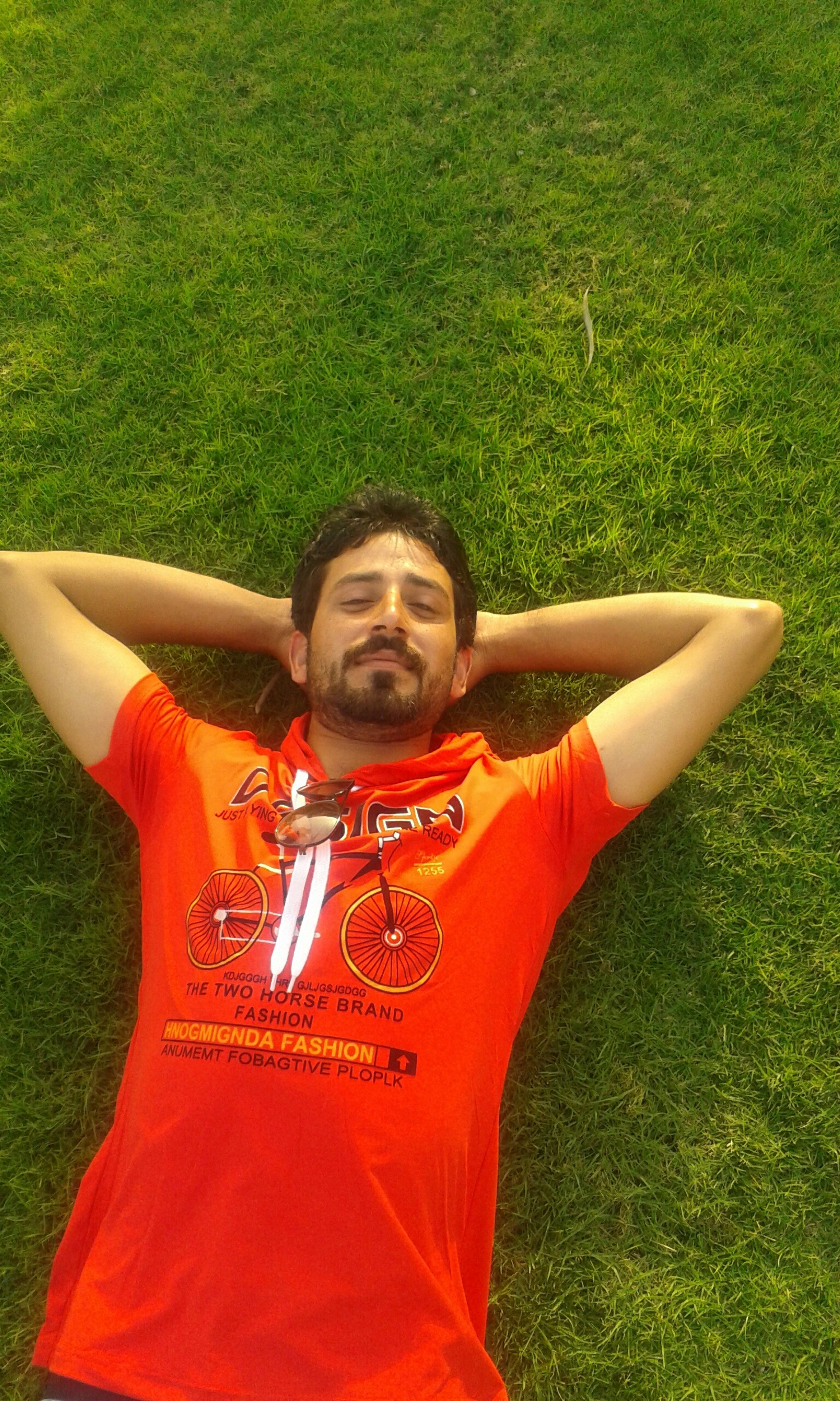 grass, leisure activity, lifestyles, green color, person, relaxation, grassy, sitting, casual clothing, field, childhood, red, looking at camera, smiling, park - man made space, front view, portrait, high angle view