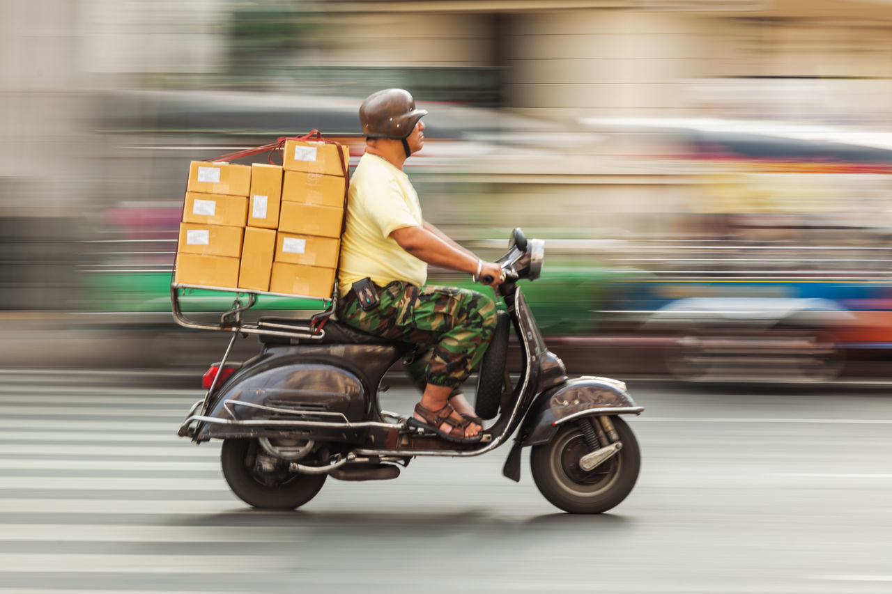 transportation, real people, mode of transport, one person, men, full length, blurred motion, land vehicle, road, street, motion, day, riding, outdoors, side view, lifestyles, reflective clothing, people