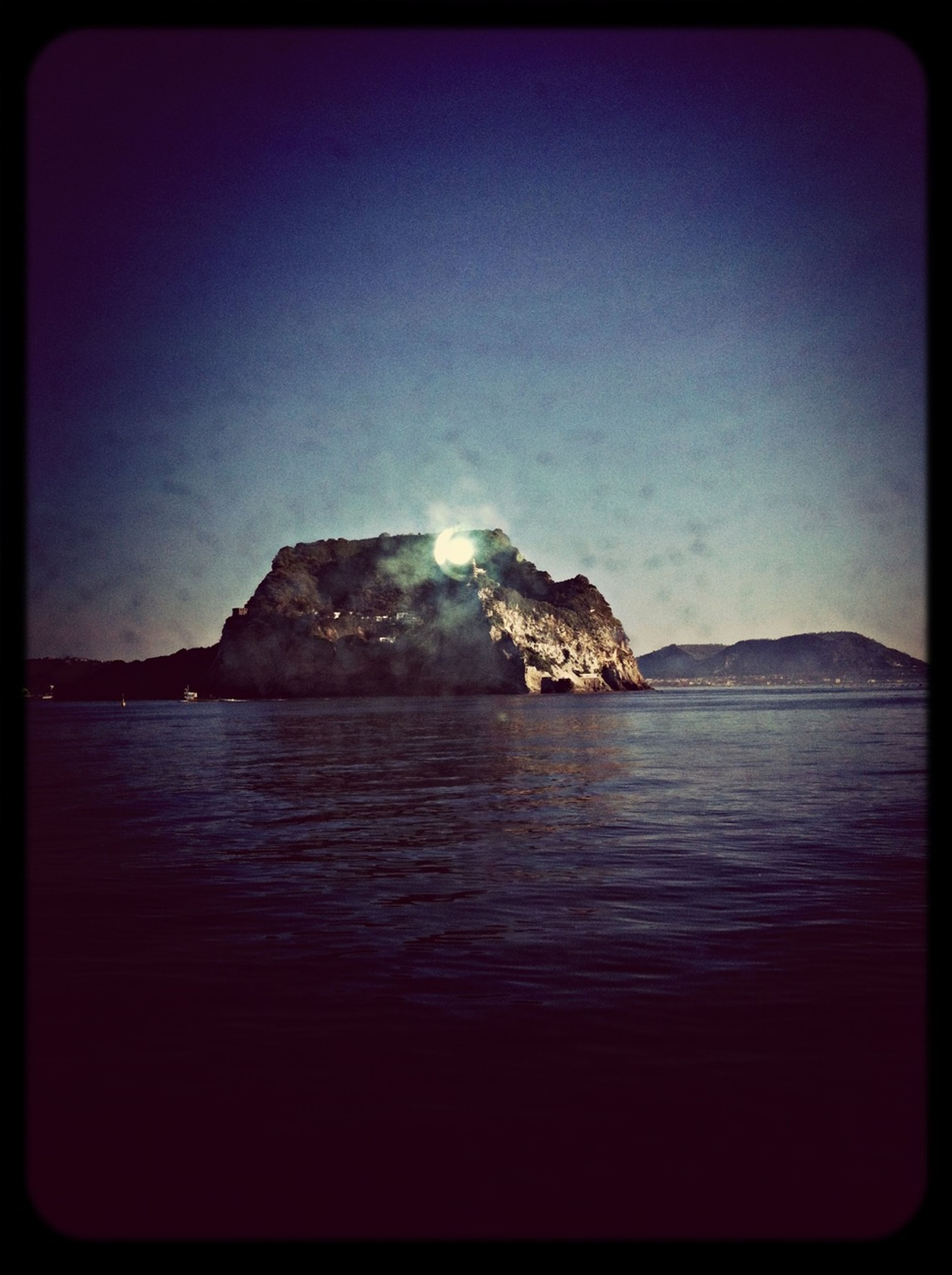 transfer print, water, auto post production filter, scenics, tranquil scene, sea, tranquility, beauty in nature, clear sky, waterfront, nature, mountain, copy space, rock formation, idyllic, blue, rock - object, sky, outdoors, rock