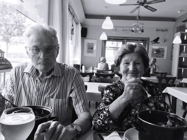 Sitting Indoors  Lifestyles Front View Waist Up Leisure Activity Three Quarter Length Person Casual Clothing Restaurant Looking At Camera Young Adult Fun Enjoyment Focus On Foreground Black And White Black & White People In Black And White Two People Elders Older Couple Enjoying A Meal Enjoying Life Eating Out Eating In Antwerp