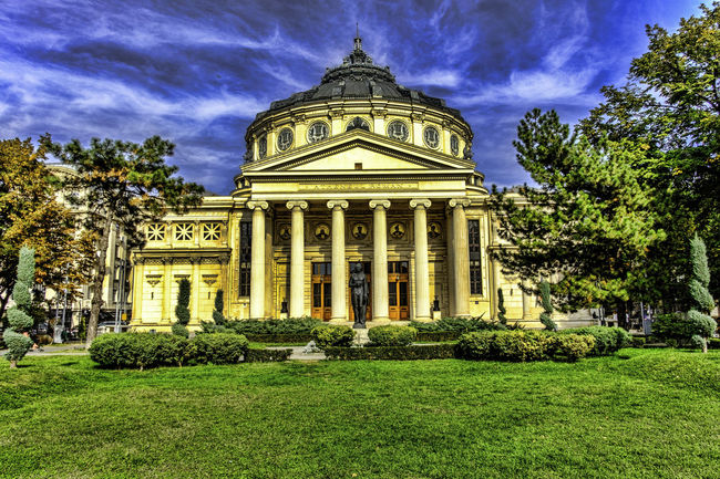 Image with Romanian Athenaeum Architecture Building Exterior Built Structure City Cloud - Sky Day Dome Government Building Grass History No People Outdoors Sculpture Sky Statue Travel Destinations Tree