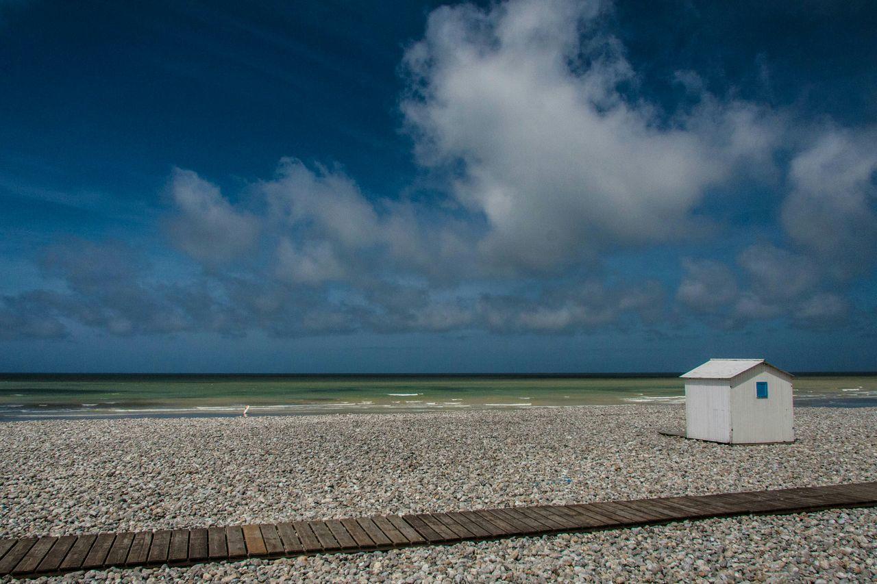 Beach Hut On Beach Against Cloudy Sky