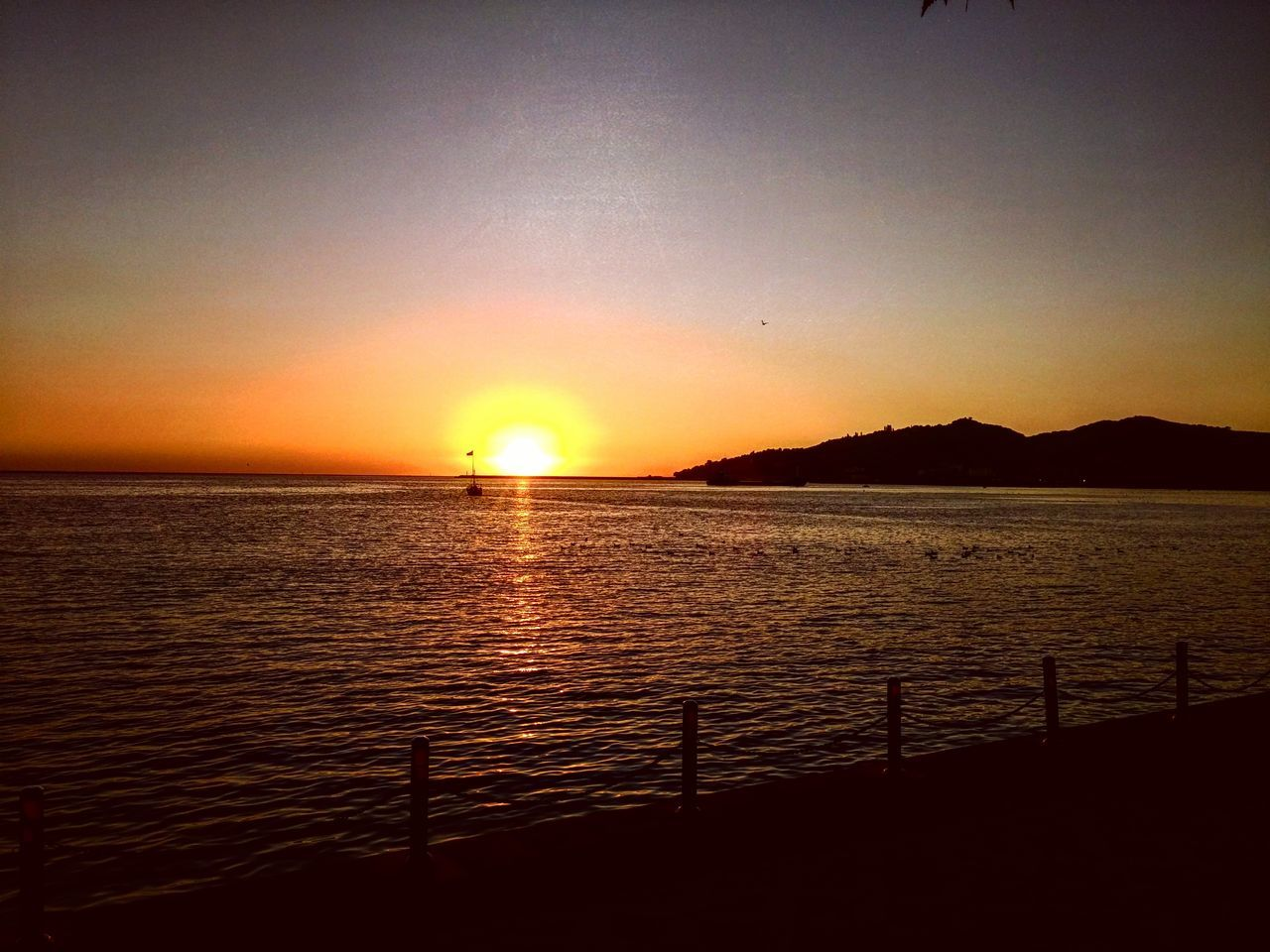 sunset, sun, scenics, beauty in nature, nature, tranquil scene, tranquility, sea, silhouette, sunlight, no people, orange color, idyllic, sky, outdoors, water, clear sky, summer, travel destinations, mountain, horizon over water, day