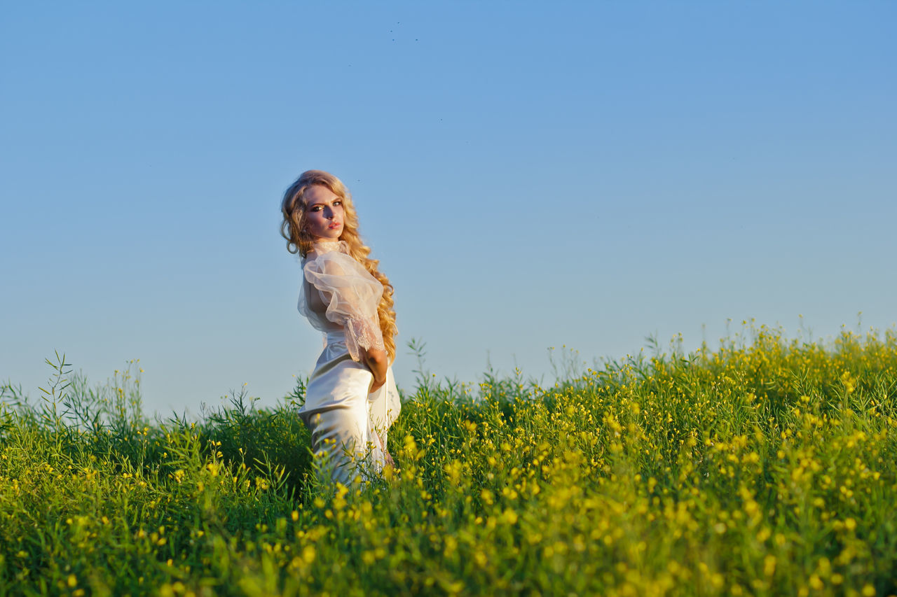 Blond Hair Blouse Bride Carefree Clear Sky Editorial  Editorial Fashion Editorialphotography Field Flower Grass Happiness Leisure Activity Long Hair Nature One Woman Only Rural Scene Sky Smiling Three Quarter Length Wedding Wedding Day Wedding Dress Wedding Photography Cover White Dress
