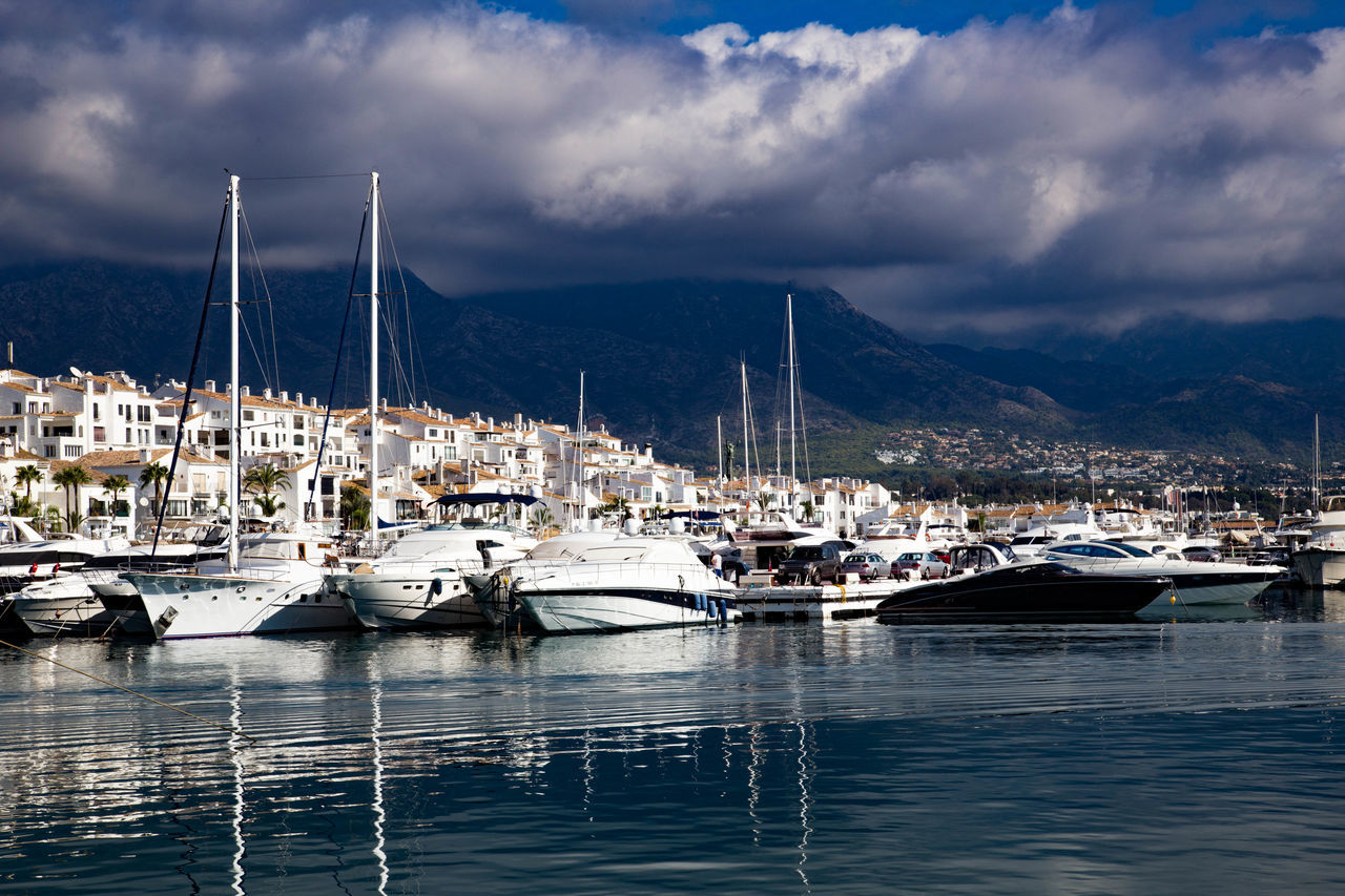 Boats Moored At Harbor In City Against Cloudy Sky