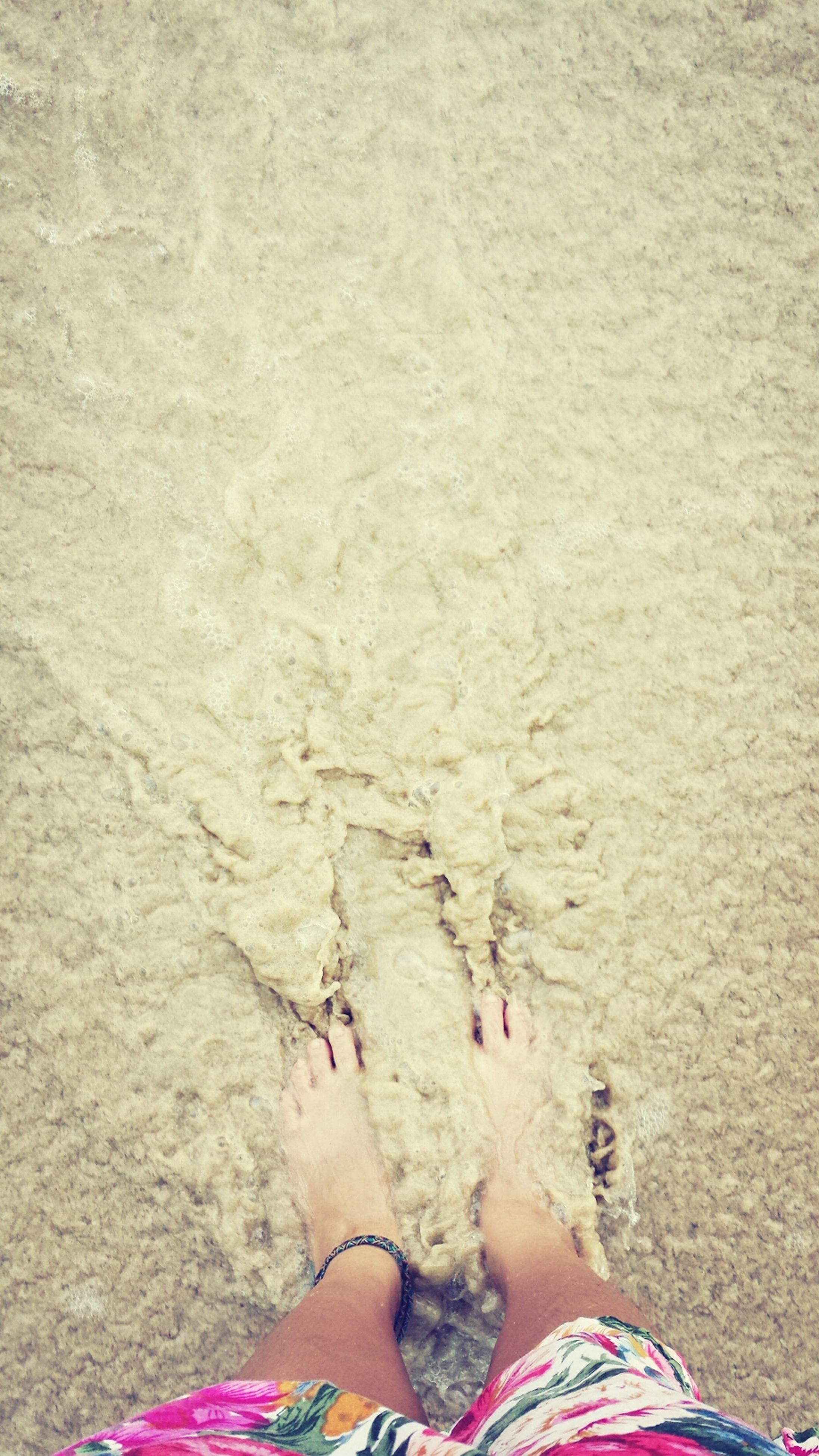 low section, person, lifestyles, leisure activity, water, beach, personal perspective, high angle view, standing, sand, human foot, barefoot, sea, shore, vacations, day