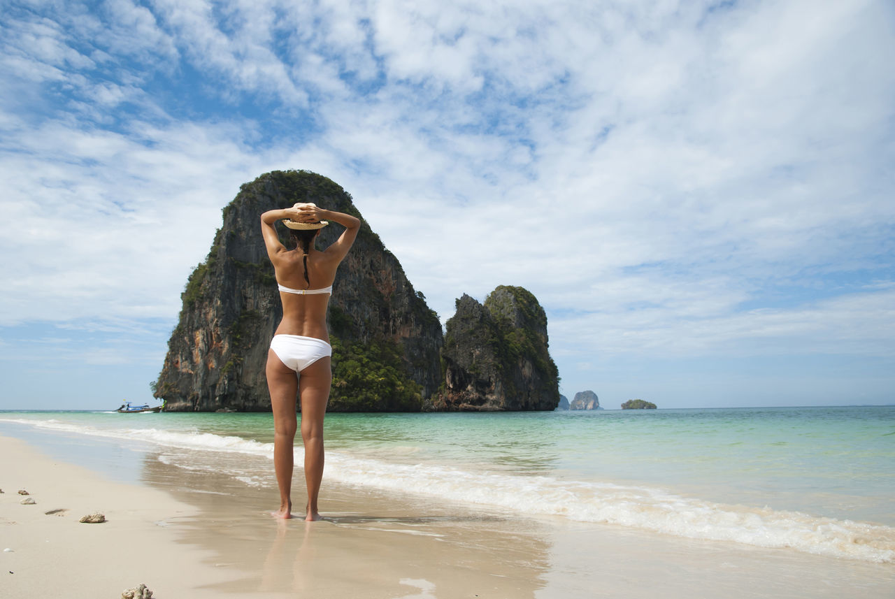 Woman on a sandy thai beach Asian  Beach Bikini Destination Escape Girl Hat Holiday Lifestyle Ocean Relax Residential Structure Sand Dune Sea Shore Standing Sunbathing Sunset Swimwear Tan Thai Thailand Travel Vacation People Of The Oceans
