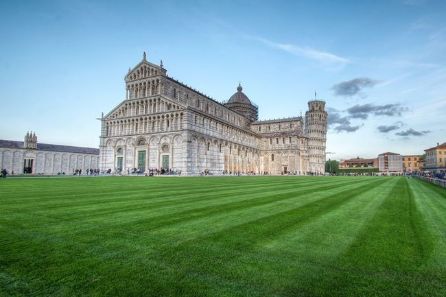 Pisa, Italy - October 22, 2016: Tourists visiting the Leaning Tower of Pisa and Pisa Cathedral in Italy. The Tower of Pisa is one of Italy's most iconic tourist attractions and is famous worldwide for its unintended tilt. Architecture Building Exterior City Clear Sky Cultures Day Government Government Building Grass History No People Outdoors Pisa Pisa Tower Politics Politics And Government Sky Travel Travel Destinations