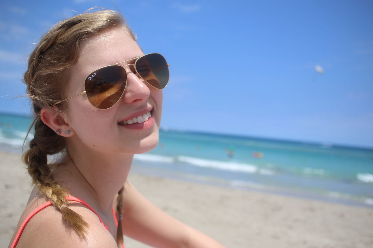 sunglasses, sea, beach, water, outdoors, one person, vacations, horizon over water, sky, focus on foreground, day, nature, sand, real people, smiling, summer, beauty in nature, young adult, leisure activity, happiness, young women, beautiful woman, headshot, portrait, close-up, clear sky