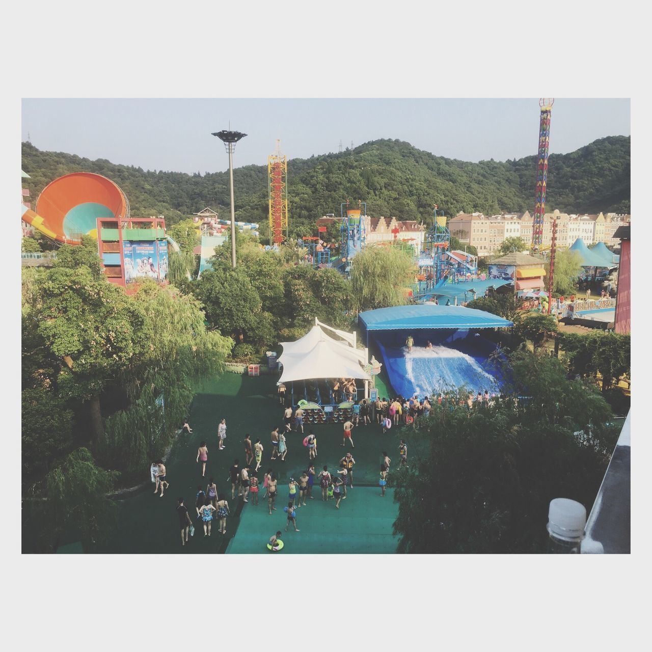 large group of people, enjoyment, water, outdoors, clear sky, tree, architecture, day, swimming pool, real people, crowd, nature, sky, people