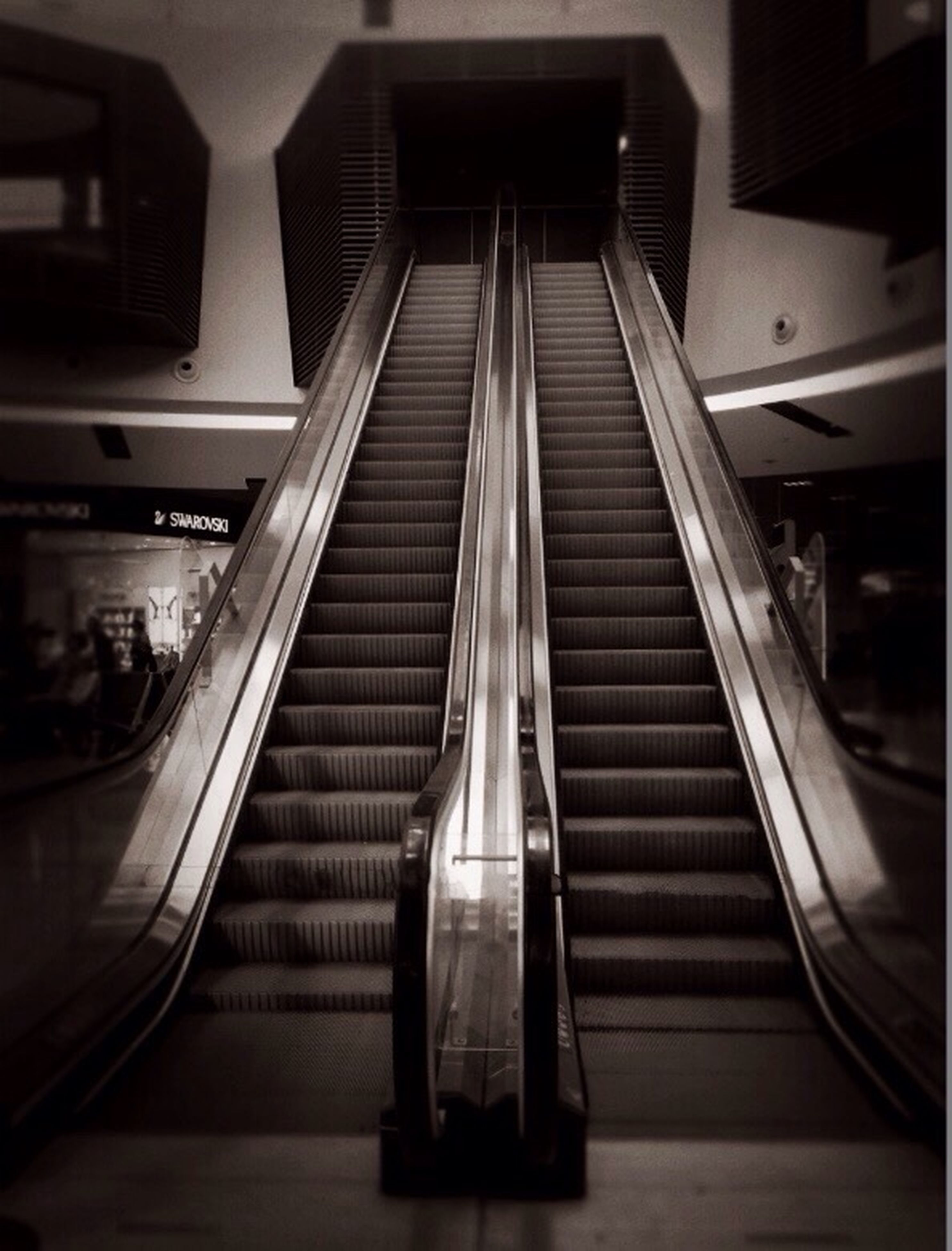 indoors, steps, steps and staircases, staircase, railing, escalator, architecture, built structure, low angle view, modern, technology, building, no people, illuminated, diminishing perspective, stairs, convenience, reflection, day, the way forward