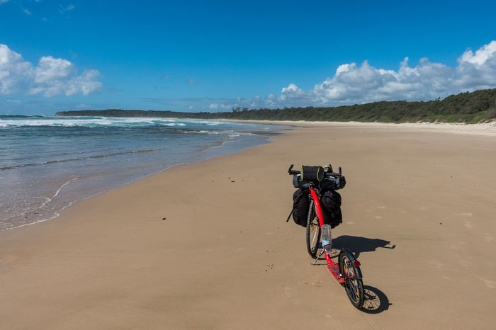 Kickbike on sandy beach with blue sky Beach Bicycle Coastline Day Escapism Horizon Over Water Kickbike Outdoors Sand Sea Seascape Shore Summer Surf Vacations Wave