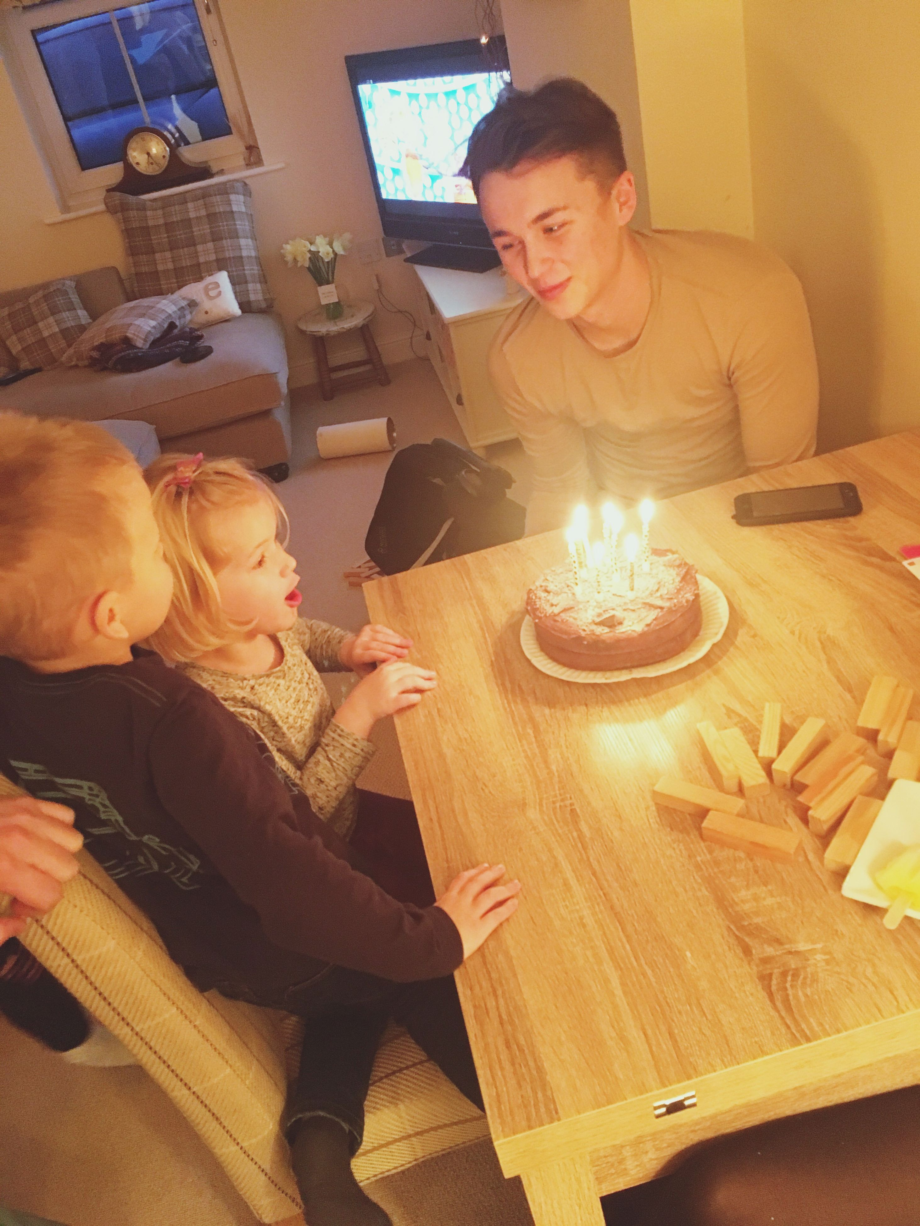 candle, indoors, women, celebration, lifestyles, burning, flame, two people, men, togetherness, sitting, adult, birthday cake, smiling, party - social event, birthday candles, happiness, home interior, young women, people, young adult, heat - temperature, cheerful, gift, adults only