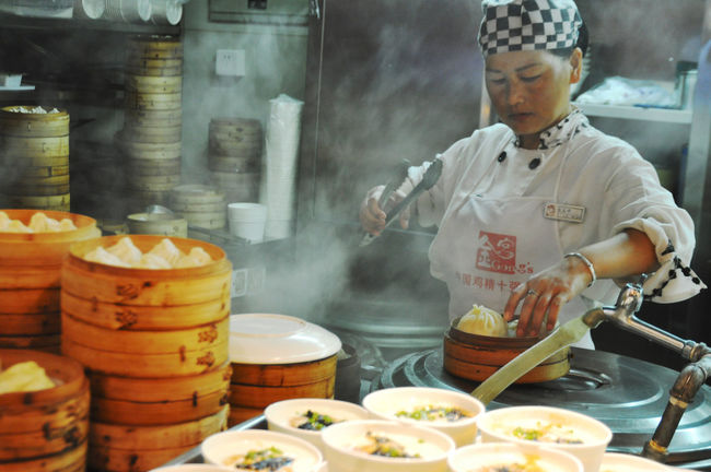 WOman busy cooking in restaurant in Shanghai, China. Action Bamboo Busy Chefs China Chinese Cuisine Cooking Cooks Dining Food Indoors  Kitchen Kitchens Preparation  Restaurants Shanghai Steam Steamers Tongs Uniforms Workers Working Women