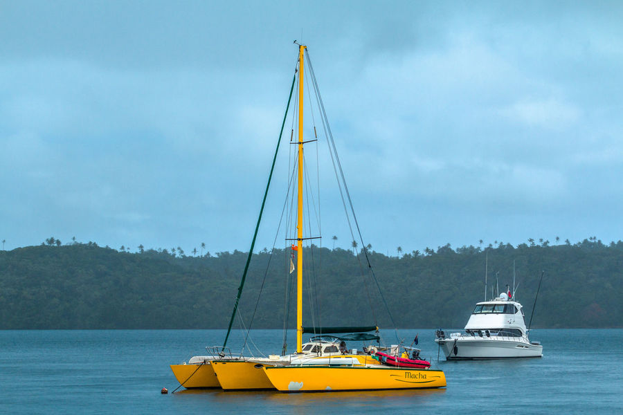 Beauty In Nature Boat Catamaran Cloud - Sky Day Katamaran Mast Mode Of Transport Mountain Nature Nautical Vessel No People Outdoors Sailboat Sailing Sailing Boat Scenics Sea Ship Sky Tonga Transportation Water Yacht Yellow