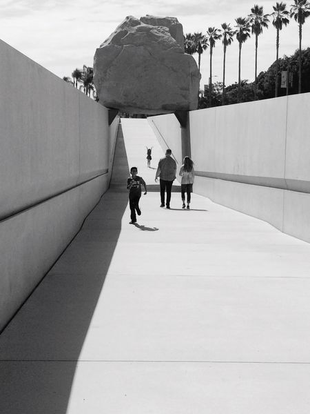 Real People Lifestyles Walking Men Day Outdoors Rear View Children Jump For Joy Black & White Geometric Shadows Shadows & Lights Shadow Geology Rock - Object Boulder Suspended Built Structure Architecture Palm Trees Southern California Boy Running Girl Jumping For Joy