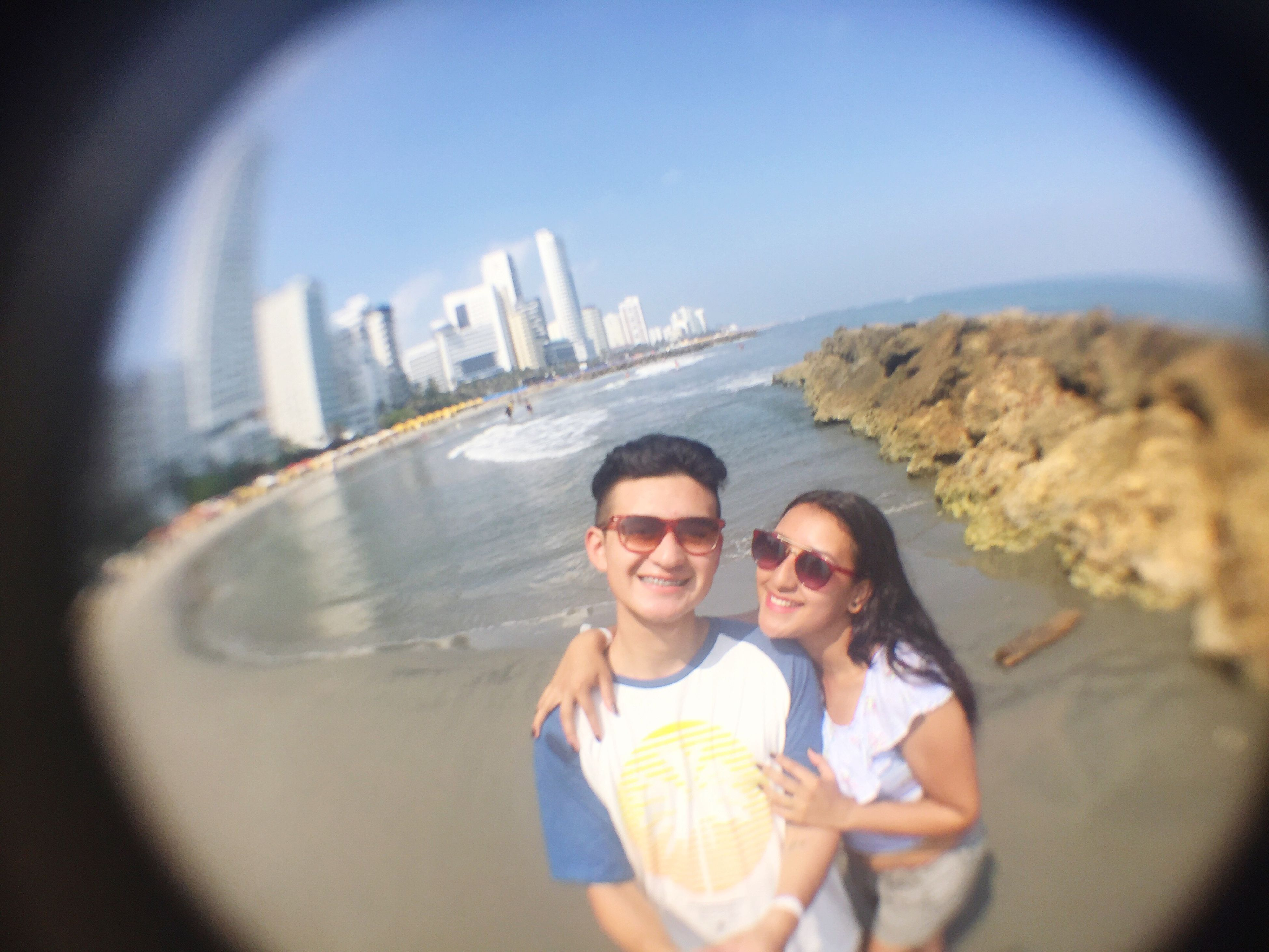 sunglasses, looking at camera, two people, young men, young adult, portrait, young women, leisure activity, real people, love, togetherness, smiling, vacations, lifestyles, front view, holding, outdoors, happiness, day, couple - relationship, fish-eye lens, men, sky, water, architecture