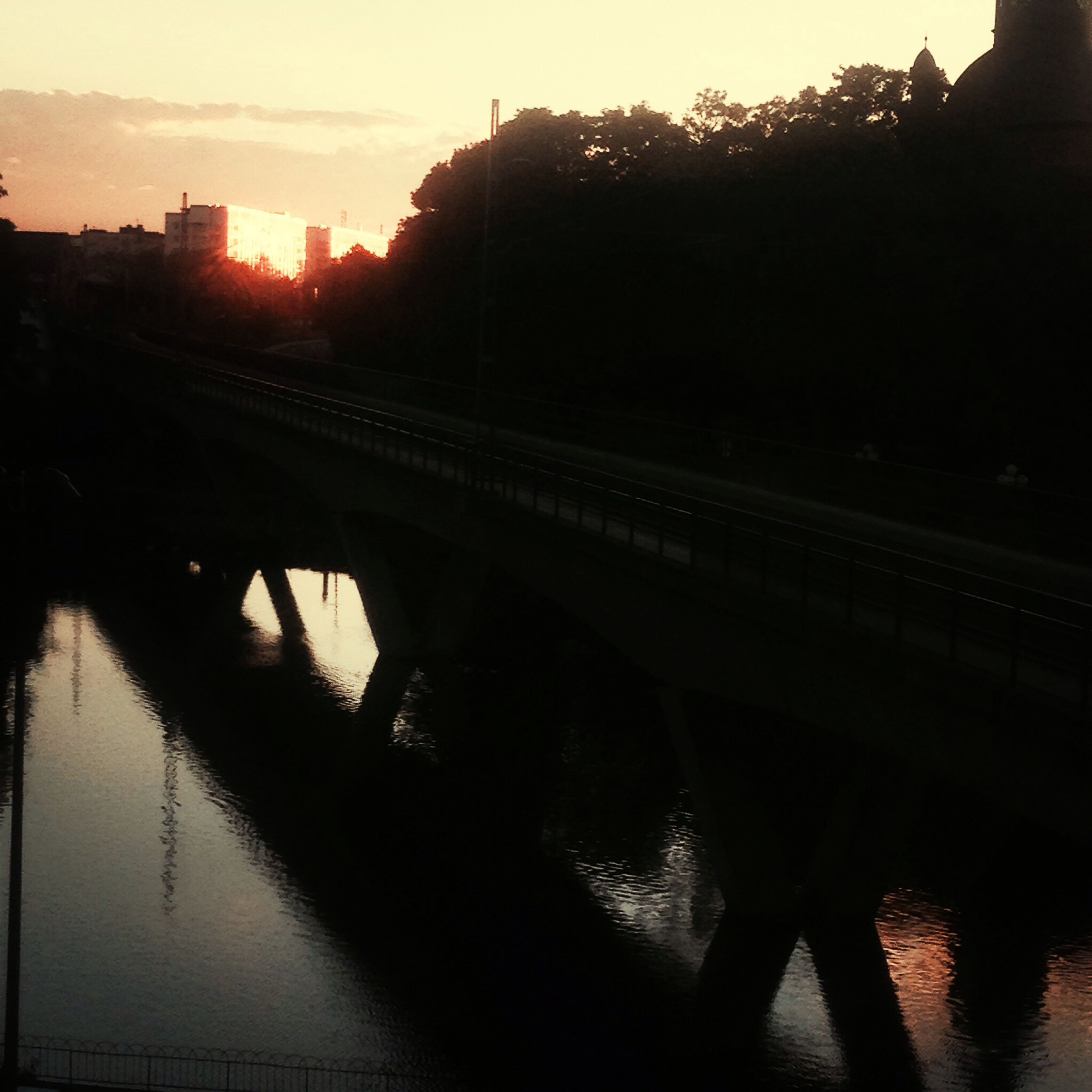 transportation, water, built structure, architecture, connection, river, bridge - man made structure, sunset, silhouette, reflection, sky, bridge, tree, canal, building exterior, dusk, railroad track, mode of transport, outdoors, waterfront