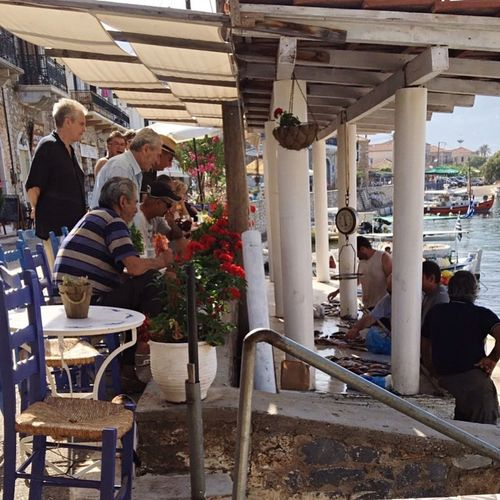 The locals gather around the fresh fish just brought in Fish Market Greece Traditional Greek Village Village Life