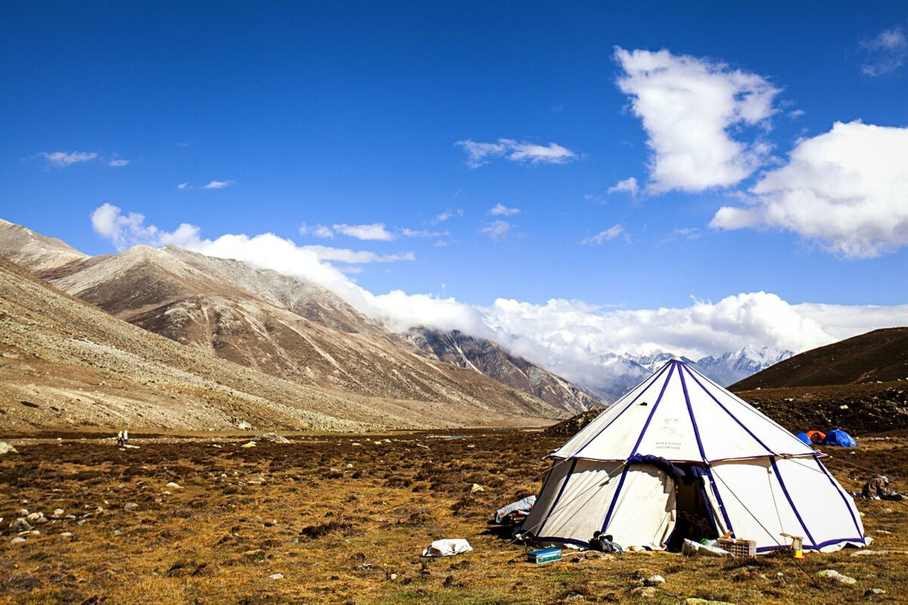 sky, mountain, tent, nature, beauty in nature, cloud - sky, landscape, scenics, mountain range, shelter, day, camping, tranquility, outdoors, blue, no people