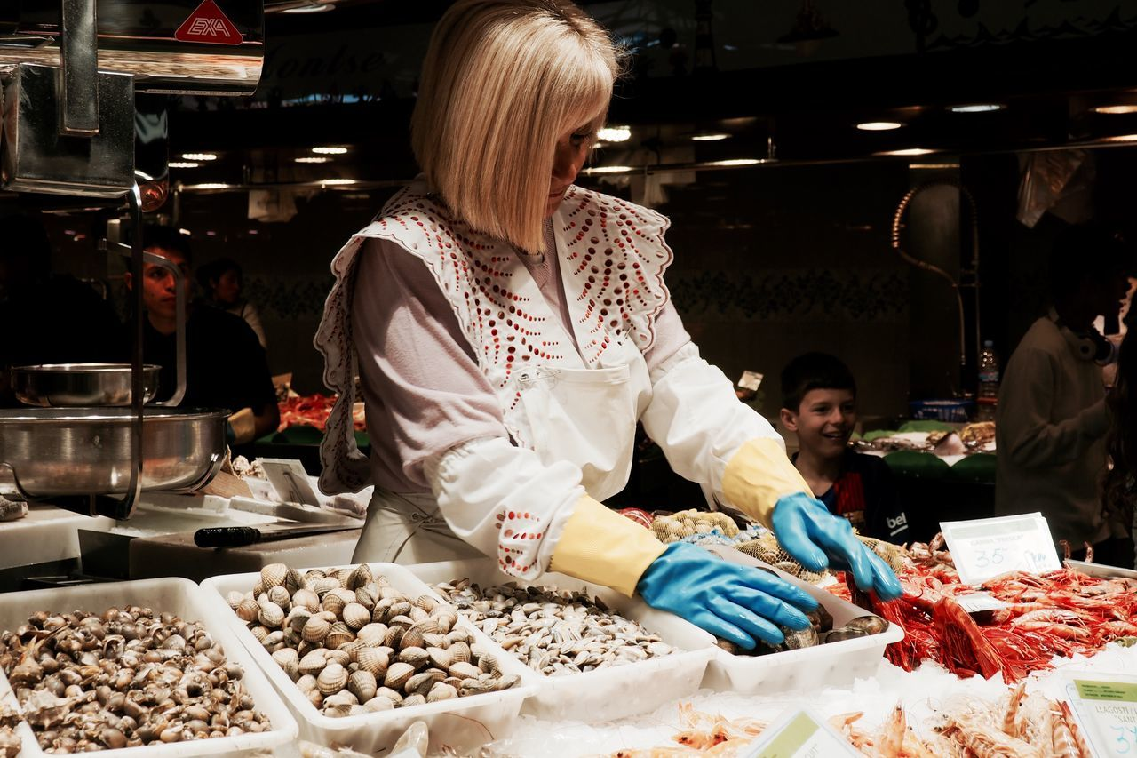 Beauty In Nature Choice Day Food Food And Drink Freshness Gloves Indoors  Market Mussels Occupation One Person People Real People Retail  Seafood Small Business Standing Sweet Food Variation Women Young Adult