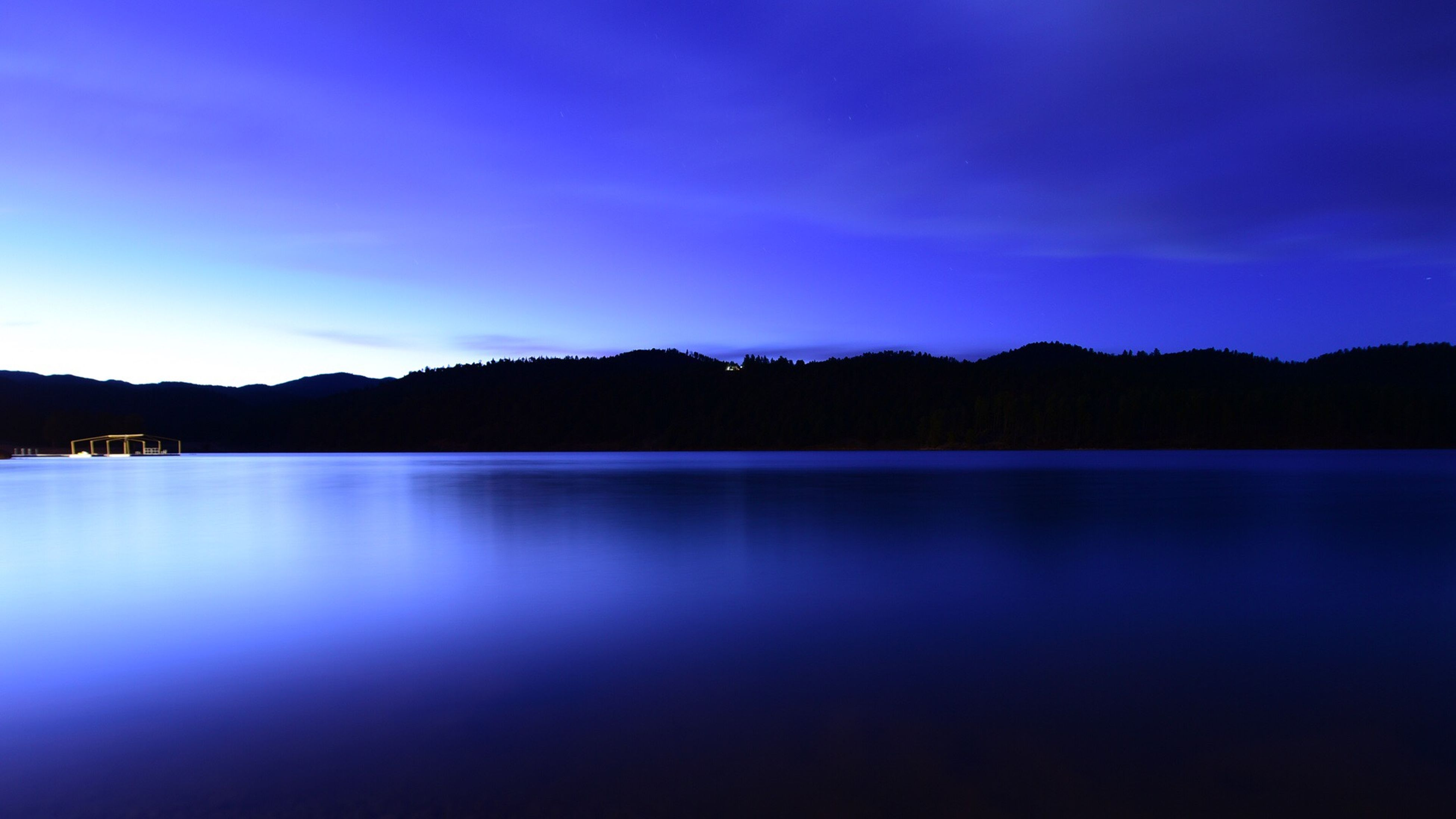 tranquil scene, blue, water, scenics, tranquility, silhouette, reflection, waterfront, lake, beauty in nature, calm, mountain, nature, idyllic, sky, majestic, cloud, countryside, non-urban scene, outdoors, no people, remote, outline, mountain range, solitude, sea, standing water, lakeside, blue color