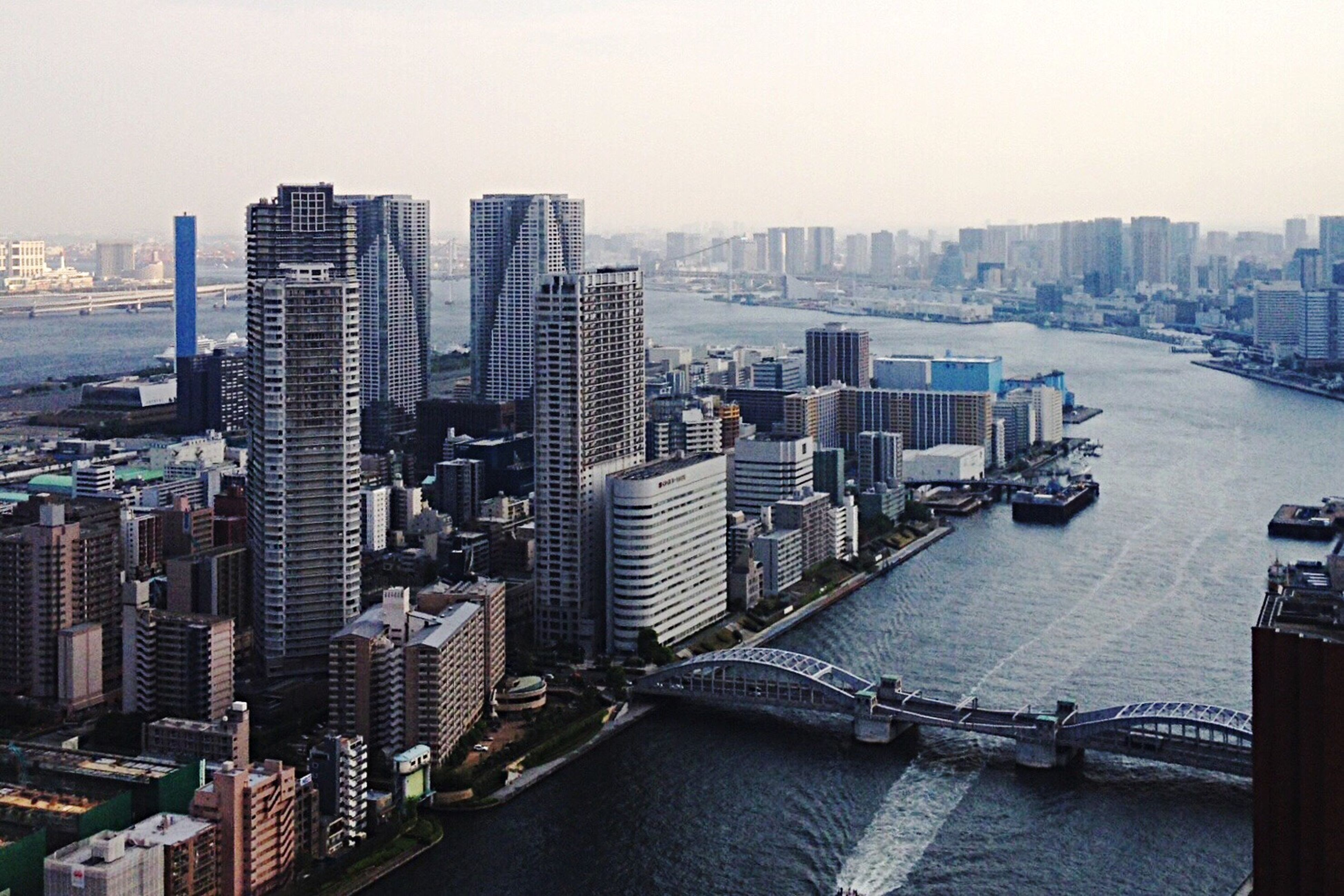 city, architecture, building exterior, built structure, cityscape, skyscraper, urban skyline, office building, tall - high, modern, tower, river, clear sky, transportation, water, skyline, financial district, city life, high angle view, sky