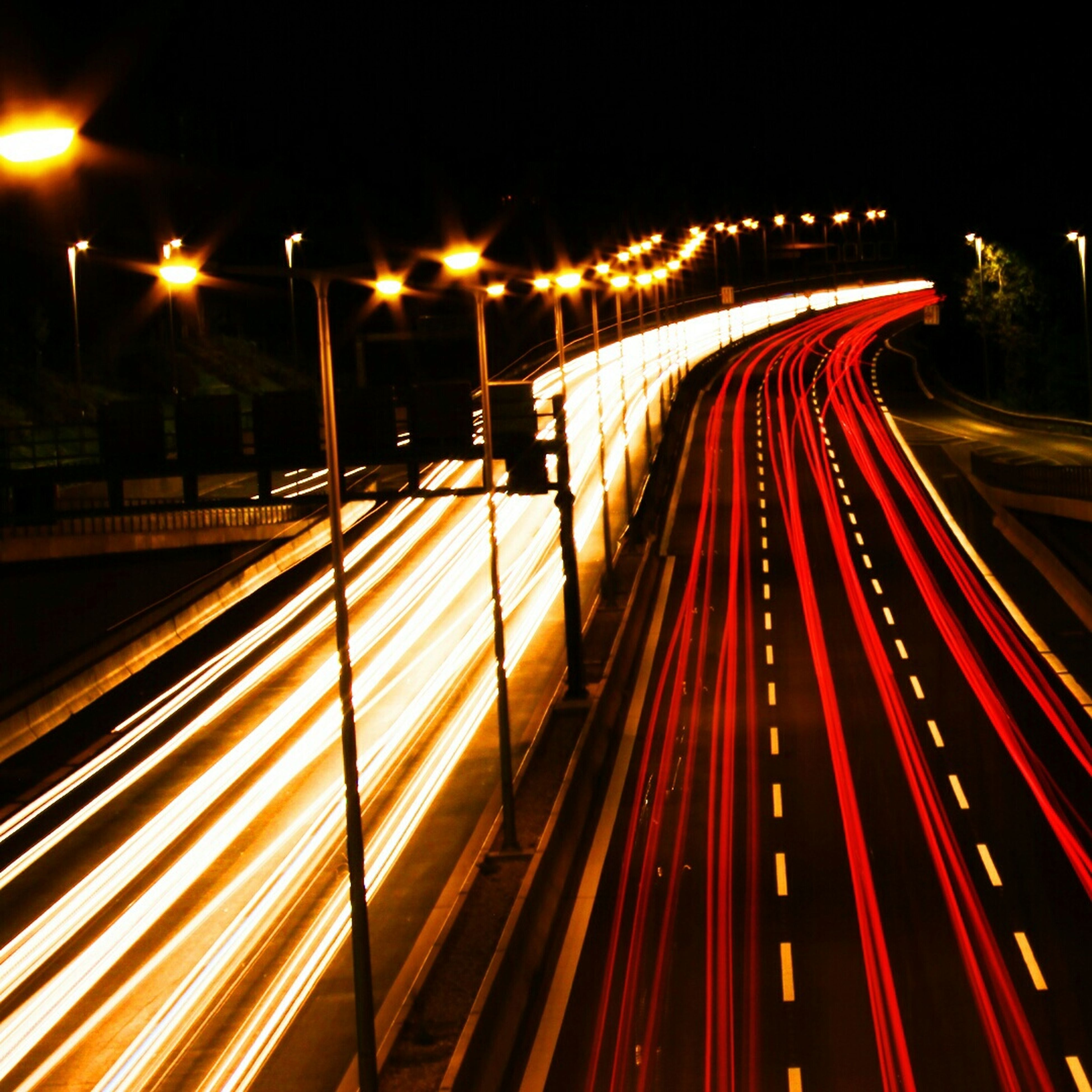 illuminated, night, long exposure, light trail, speed, transportation, motion, street light, blurred motion, road, city, traffic, the way forward, lighting equipment, street, high angle view, city life, road marking, highway, on the move