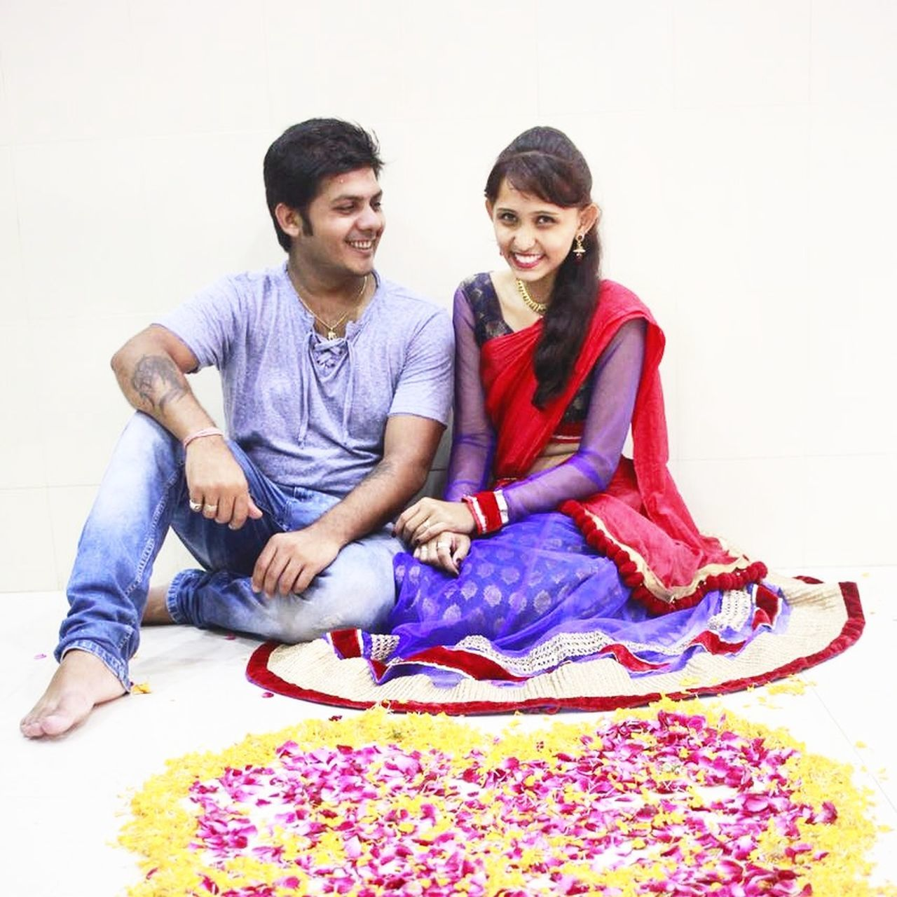 two people, togetherness, happiness, smiling, full length, casual clothing, sitting, young adult, front view, love, young men, bonding, young women, home interior, beautiful woman, sari, white background, portrait, real people, indoors, cheerful, powder paint, adult, holi, day, people, adults only