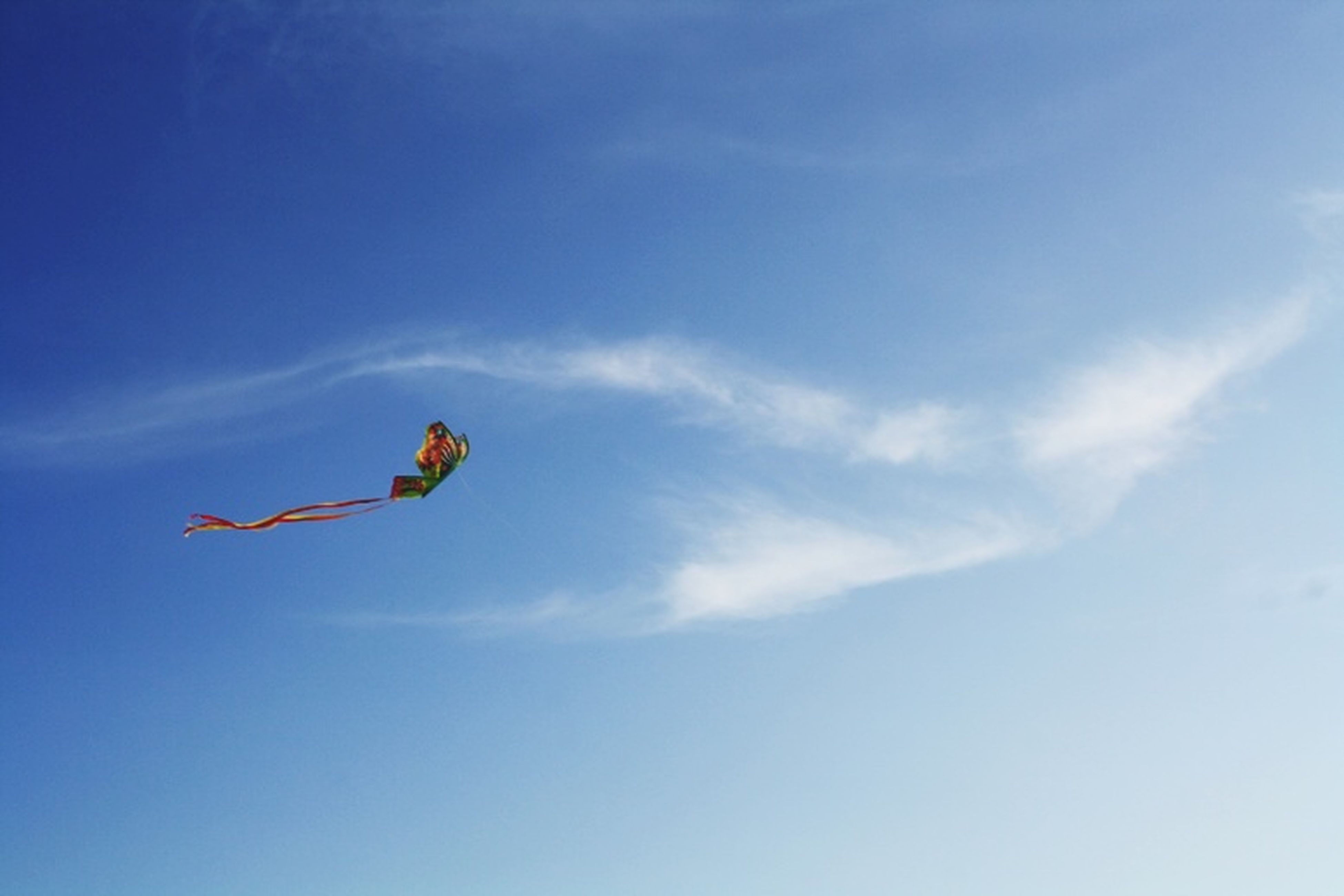 low angle view, flying, mid-air, blue, sky, cloud - sky, transportation, freedom, motion, day, kite - toy, air vehicle, outdoors, extreme sports, on the move, nature, cloud, adventure, parachute, fun