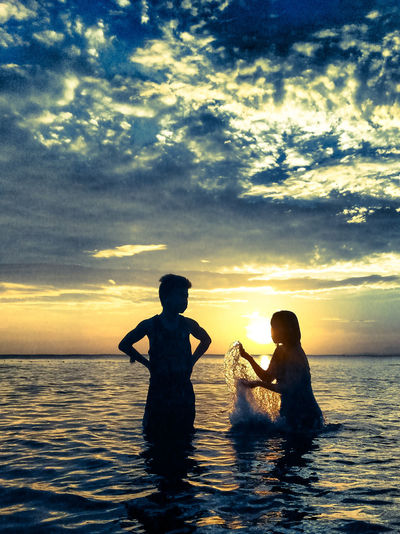 Playful children meets playful water.Sunset Child Sky Water Men Outdoors Cloud - Sky Togetherness Beach Nature People Adult