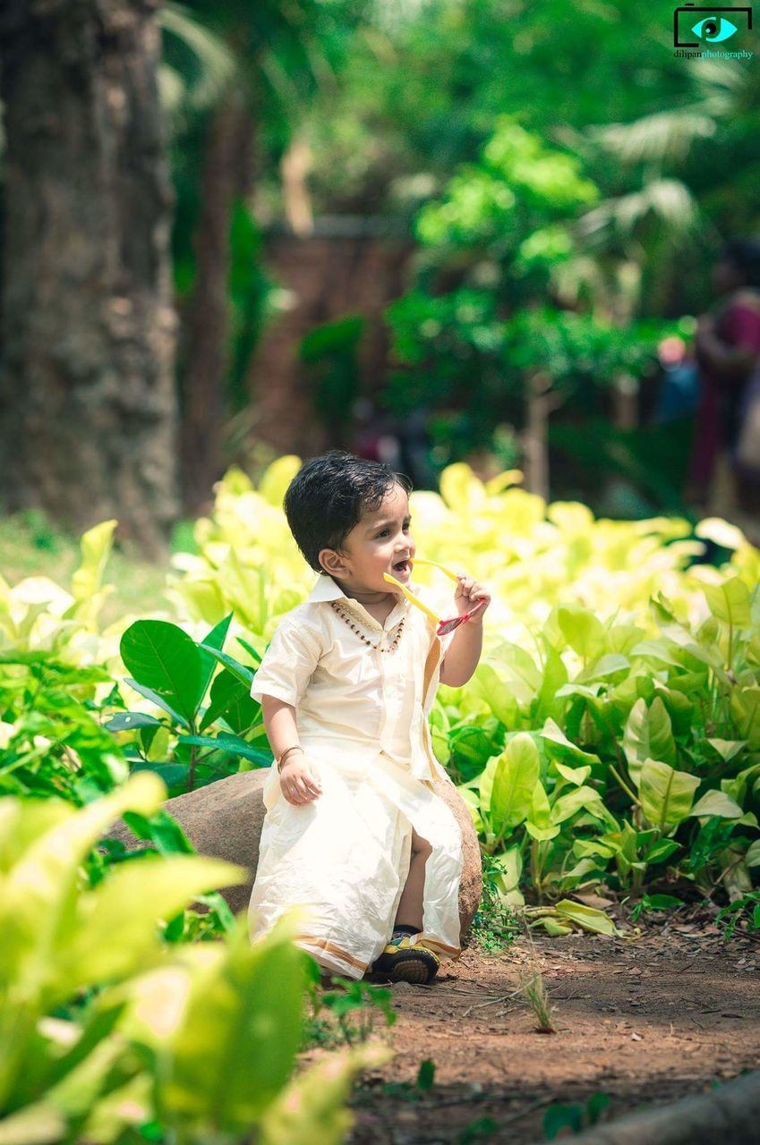 real people, one person, full length, outdoors, lifestyles, flower, girls, childhood, elementary age, day, plant, green color, front or back yard, tree, nature, growth, happiness, beauty in nature, young adult, flower head, people