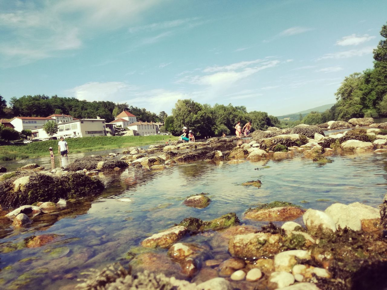 water, tree, sky, outdoors, day, large group of people, nature, river, beauty in nature, built structure, real people, architecture, people