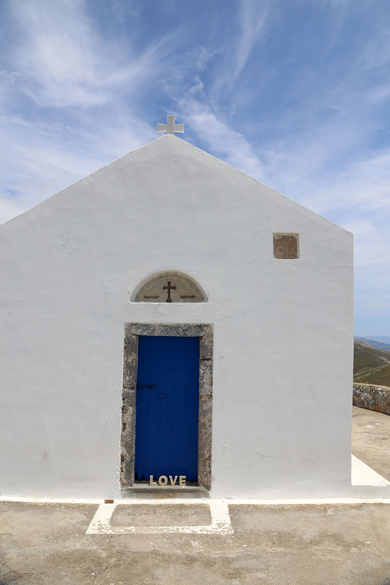 "white Chapel with cross and word ""love"" in Crete, Greece Architecture Building Exterior Built Structure Cross Day Doorway Entrance No People Outdoors Place Of Worship Religion Sky Spirituality Sunlight Whitewashed"