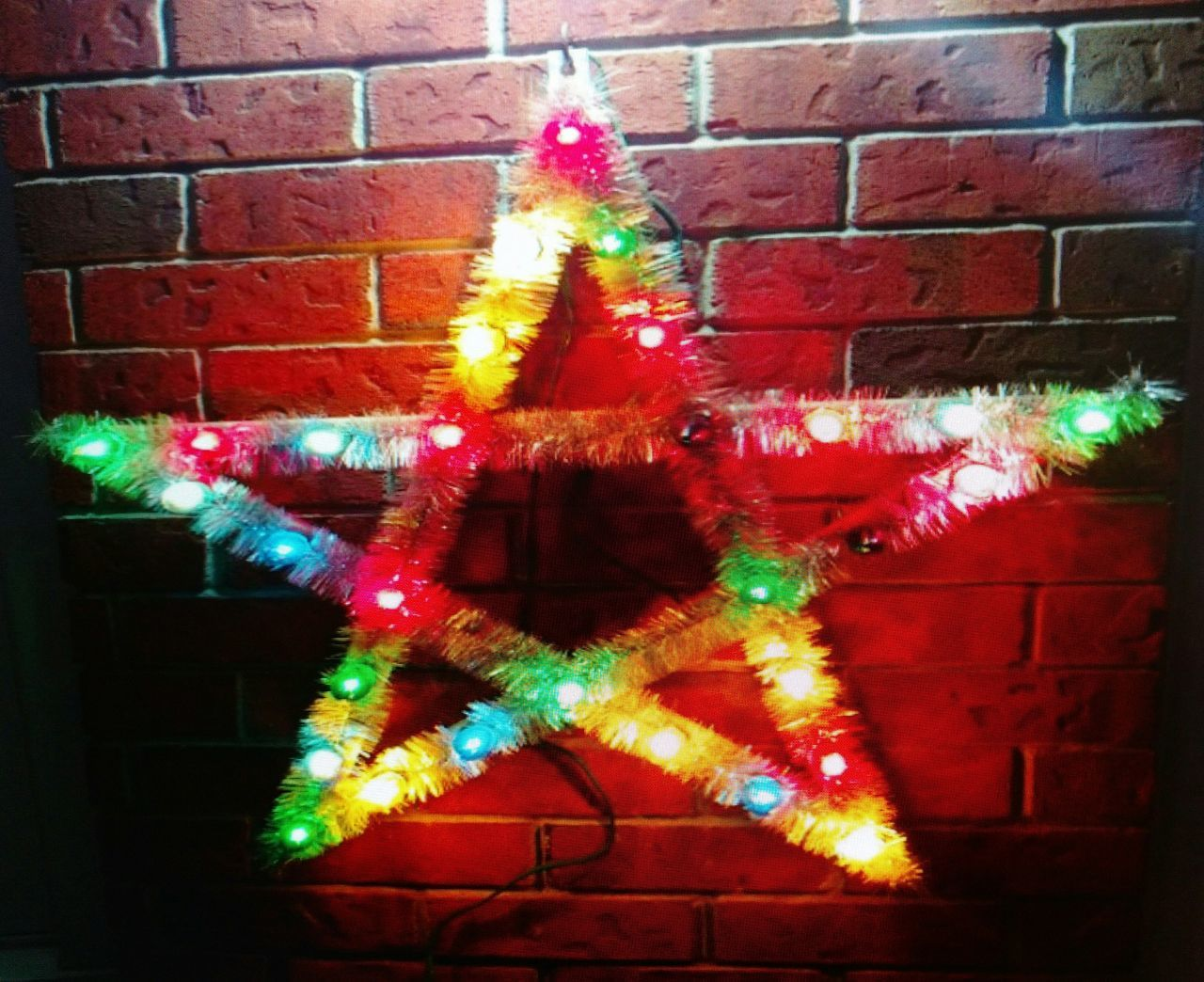 christmas, celebration, christmas tree, christmas decoration, tradition, decoration, christmas lights, holiday - event, brick wall, cultures, night, indoors, celebration event, christmas ornament, illuminated, no people, traditional festival, tree topper, hanging, building exterior, close-up
