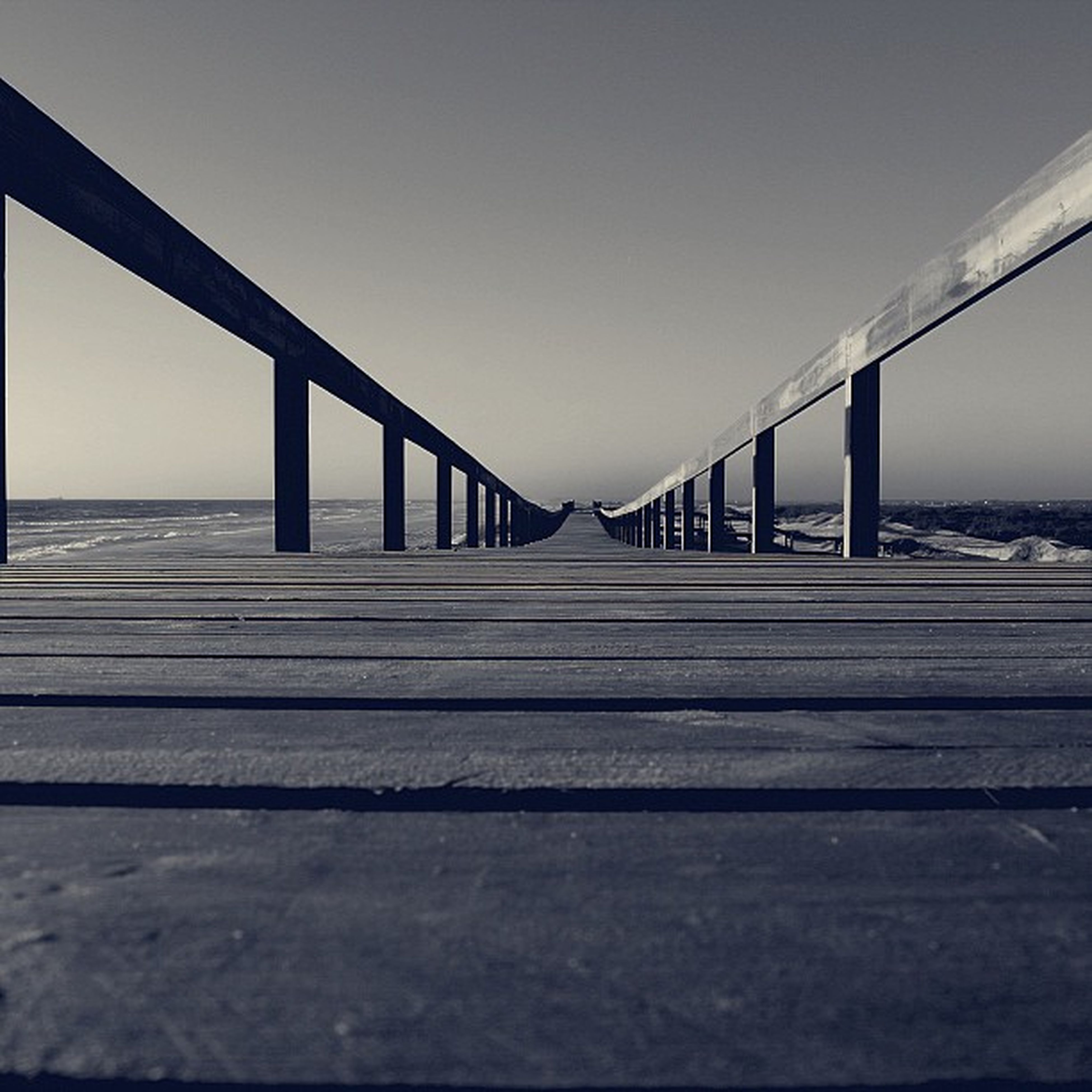 sea, clear sky, horizon over water, built structure, the way forward, railing, water, pier, sky, diminishing perspective, architecture, long, beach, connection, bridge - man made structure, bridge, surface level, tranquility, tranquil scene, copy space