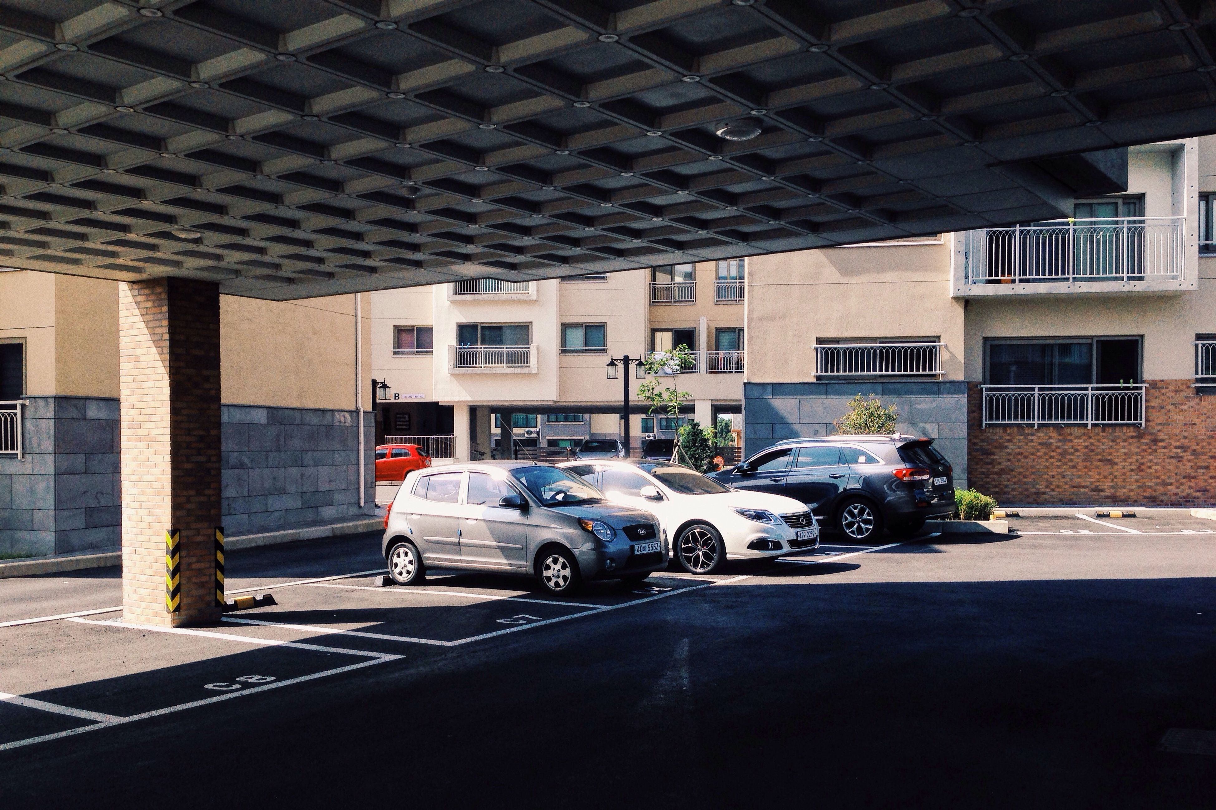 land vehicle, architecture, street, mode of transport, built structure, road, parked, parking, city, stationary, motorcycle, city street, city life, residential building, day, outdoors, parking lot, lifestyles