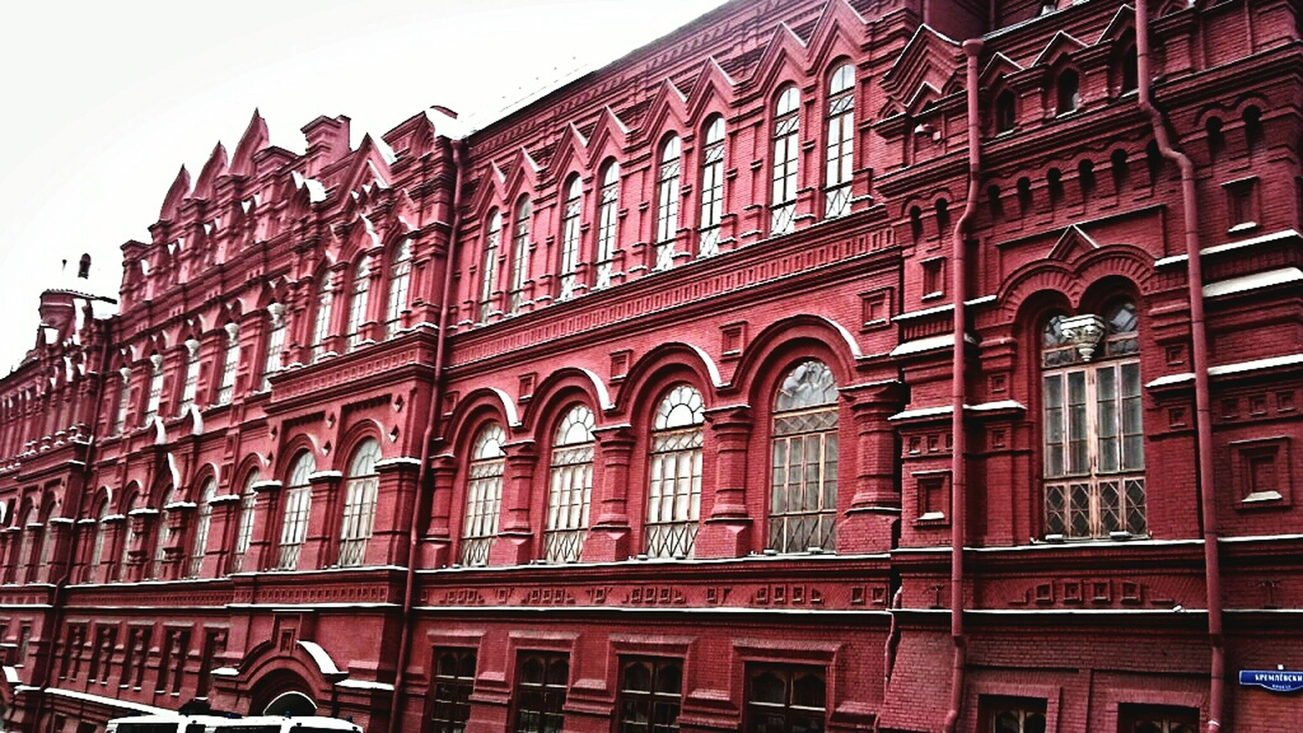 architecture, building exterior, built structure, low angle view, arch, window, city, facade, building, red, sky, day, travel destinations, outdoors, history, balcony, text, famous place, clear sky, city life