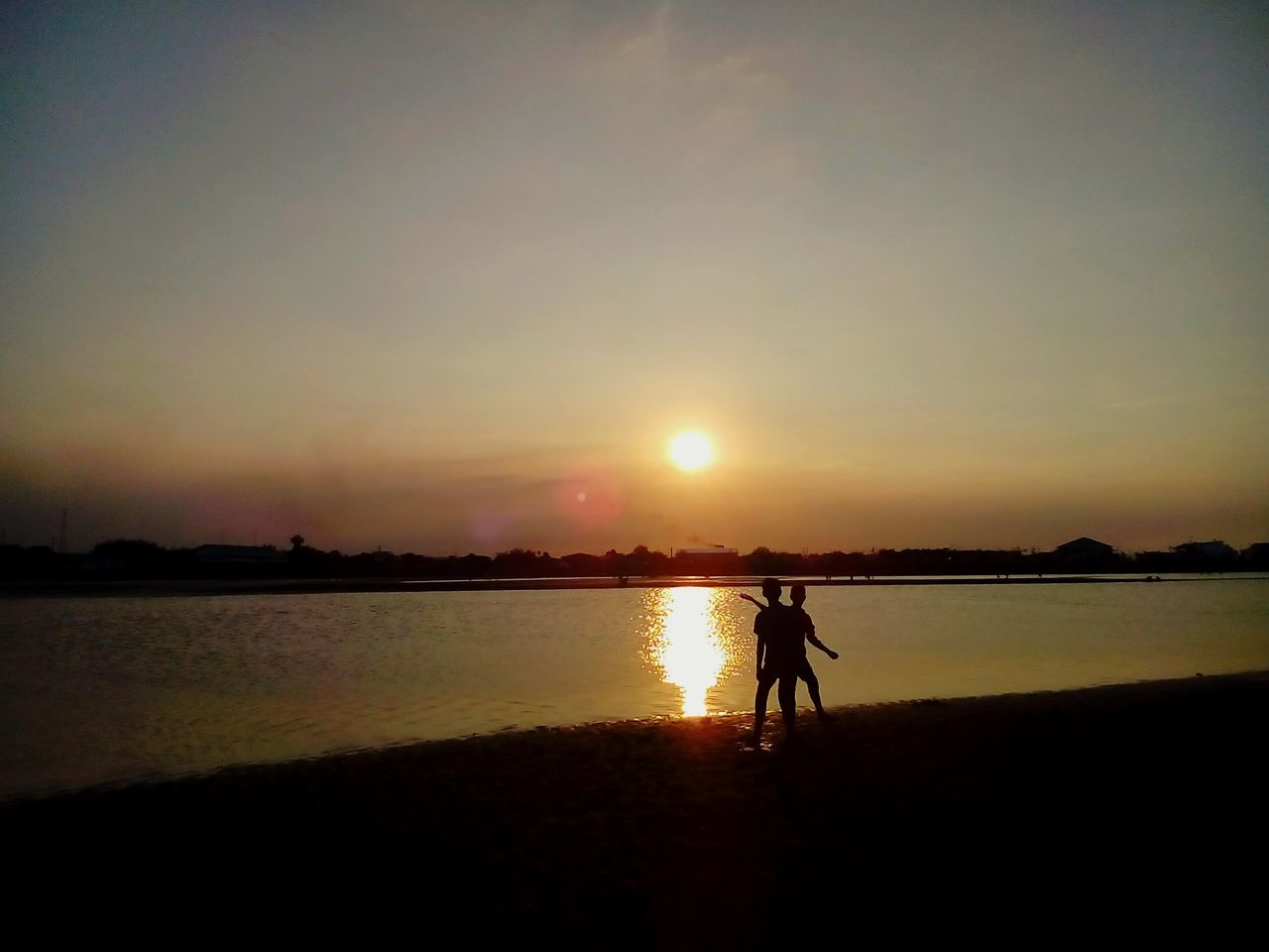 sunset, silhouette, reflection, real people, nature, water, beauty in nature, sun, full length, sky, scenics, leisure activity, men, one person, tranquil scene, standing, outdoors, tranquility, lake, lifestyles, clear sky, day, people