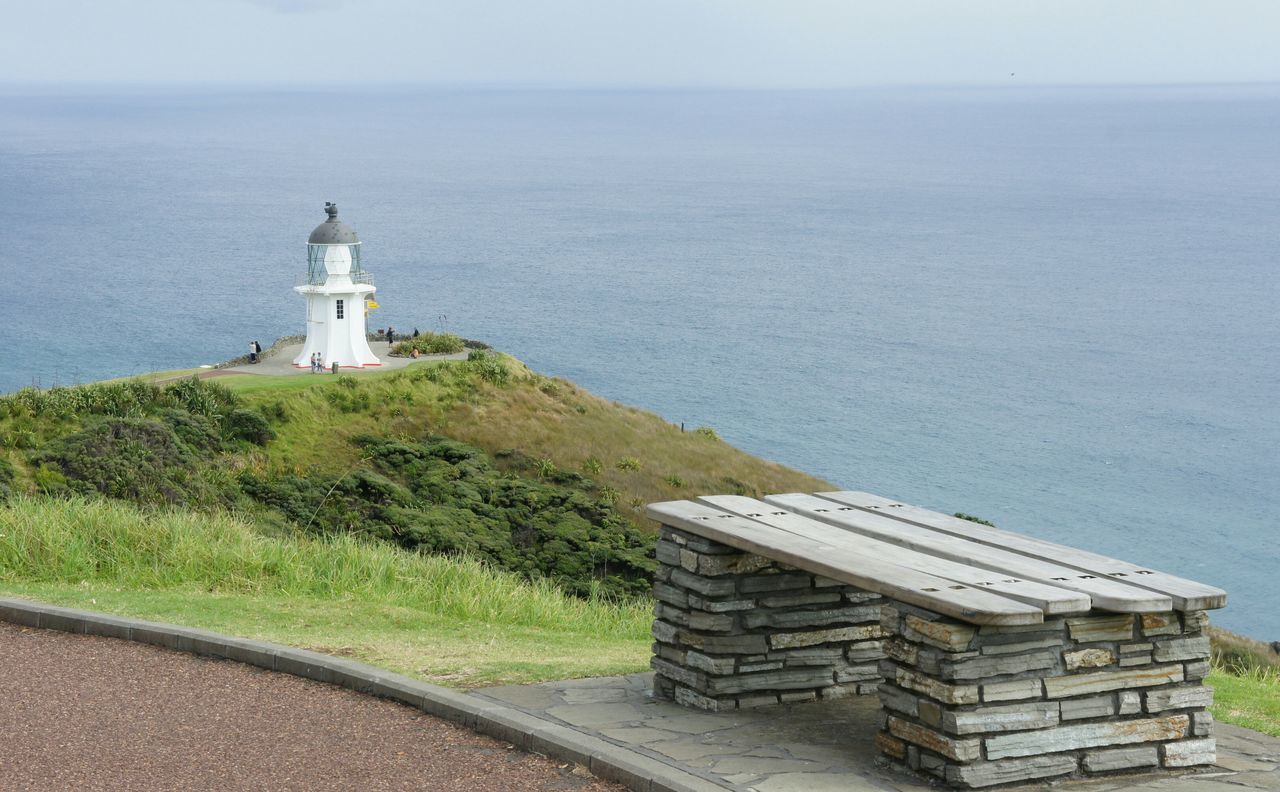 Bench And Lighthouse Against Sea